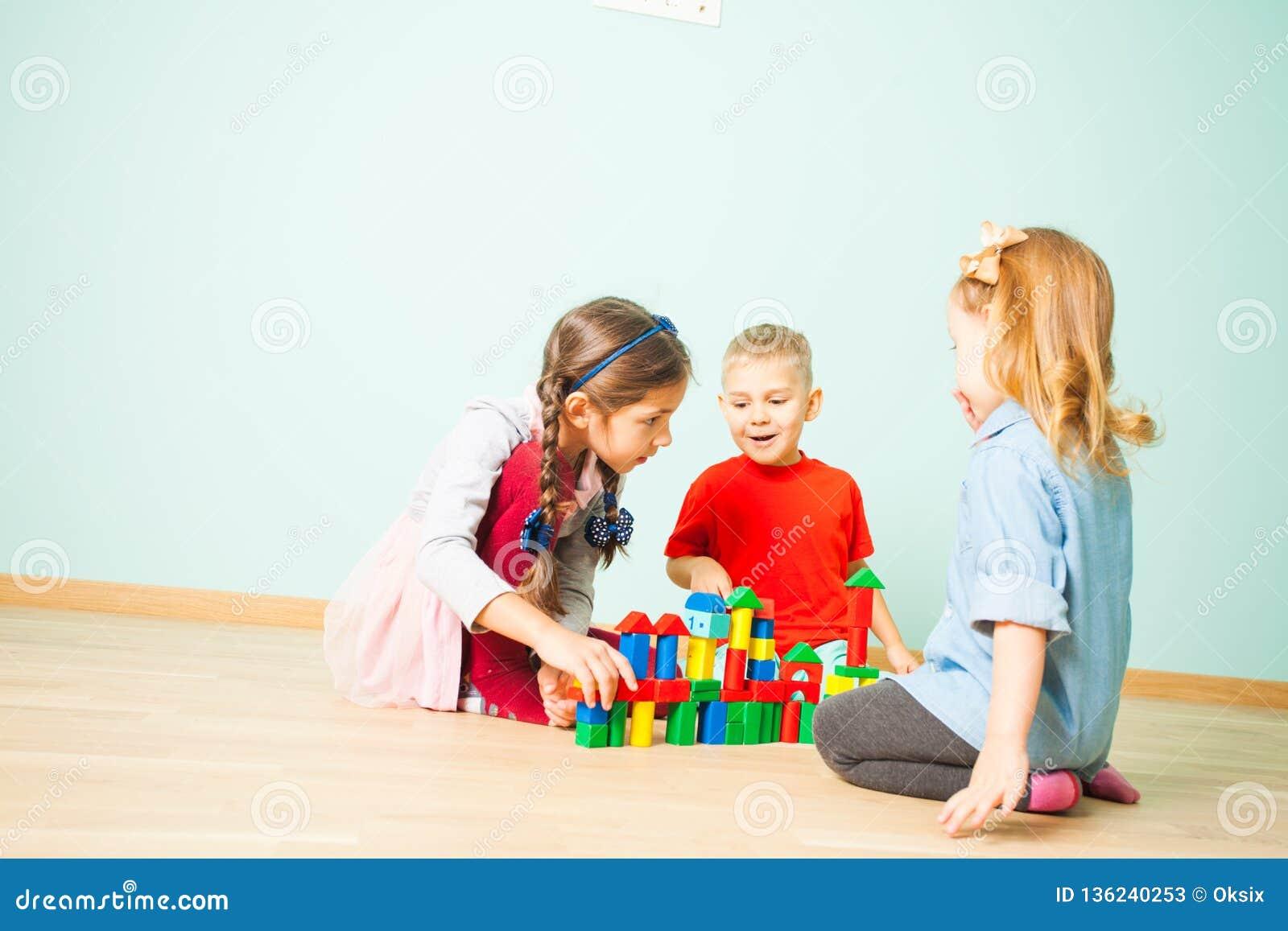 Kinderspiel an der Tagesbetreuung Drei Vorschüler, die Turm von den hölzernen Würfeln errichten