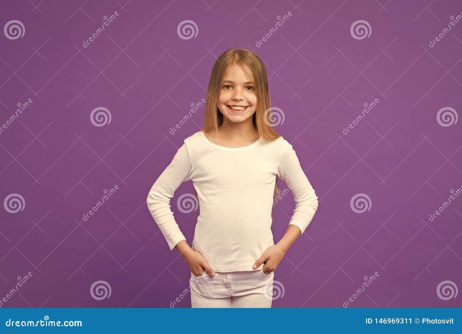 Kindertragender wei?er Pullover und Jeans, Jugendmodekonzept M?dchen mit blondes Haar lang gl?nzen Reizendes Kind mit gro?em