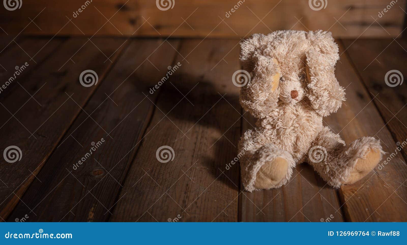 Kindesmissbrauch Teddybär, der Augen, dunklen leeren Hintergrund, Kopienraum bedeckt