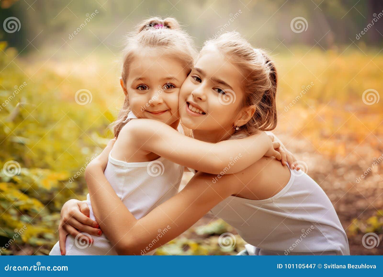 Kindheit, Familie, Freundschaft und Leutekonzept - zwei glückliche Kinderschwestern, die draußen umarmen
