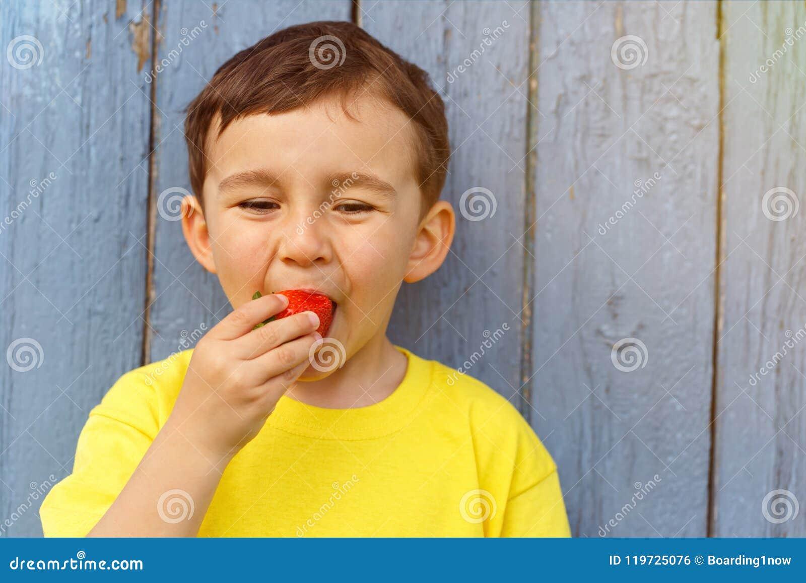 Kindjong geitje weinig jongen die de zomeraardbeien eten van het aardbeifruit