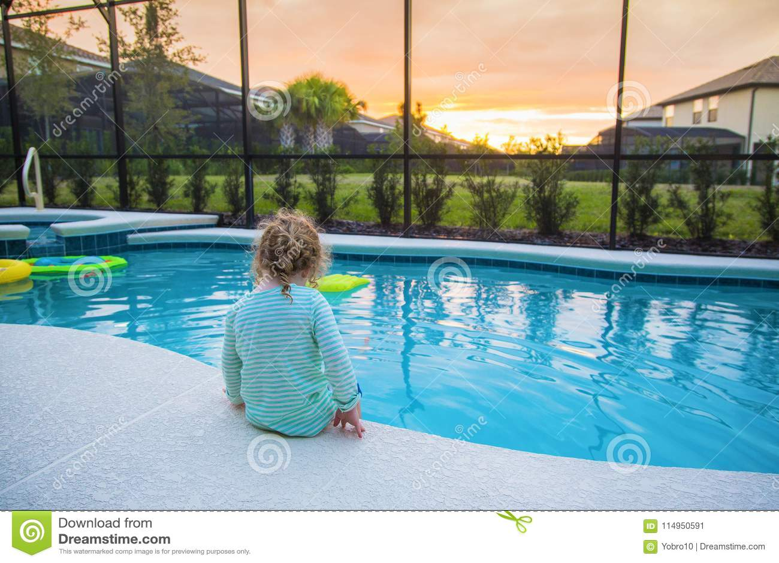 Kindzitting op de rand van een zwembad op een warme de zomerdag