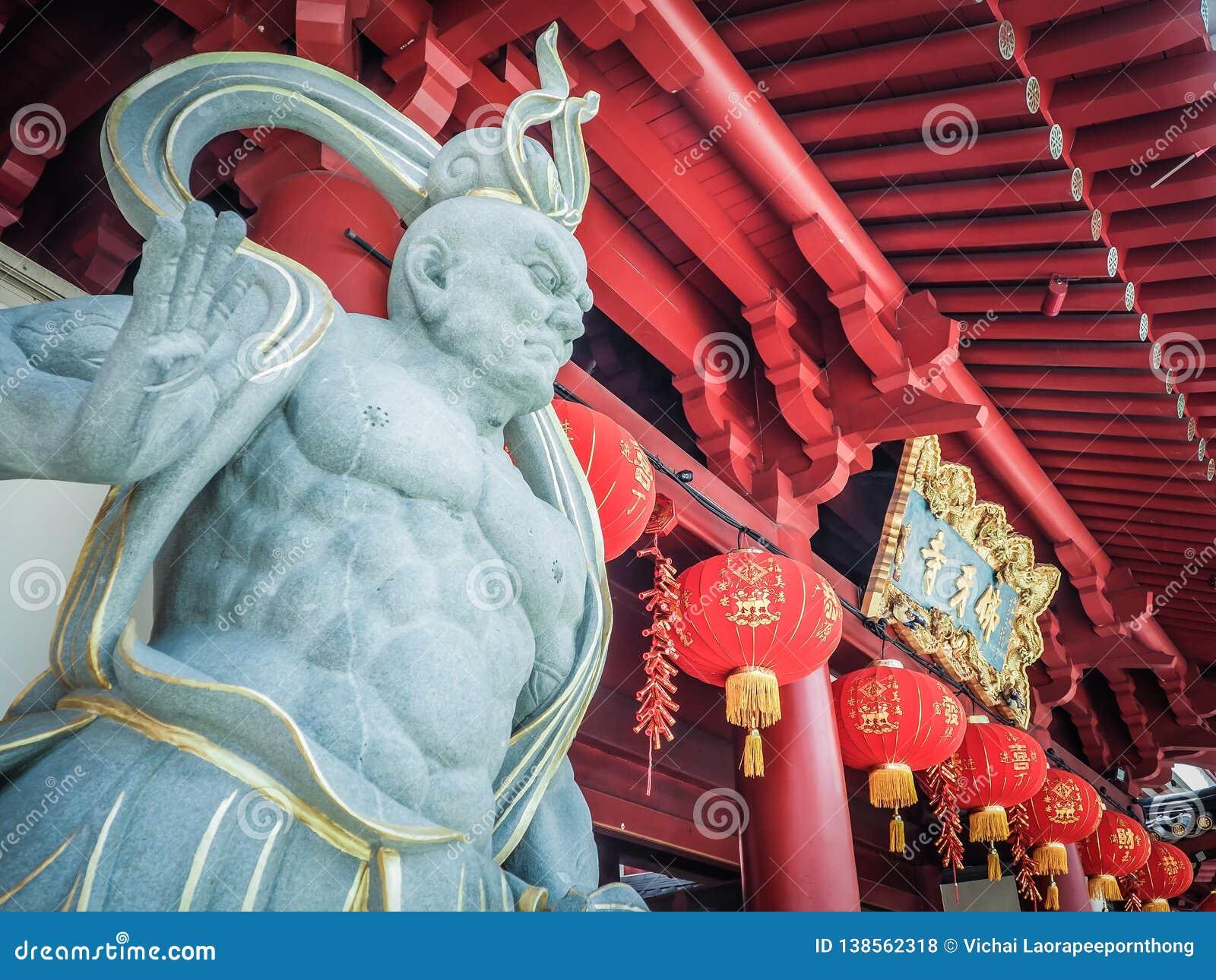 Kinesisk gudstenstaty framme av templet för Buddhatandrelik