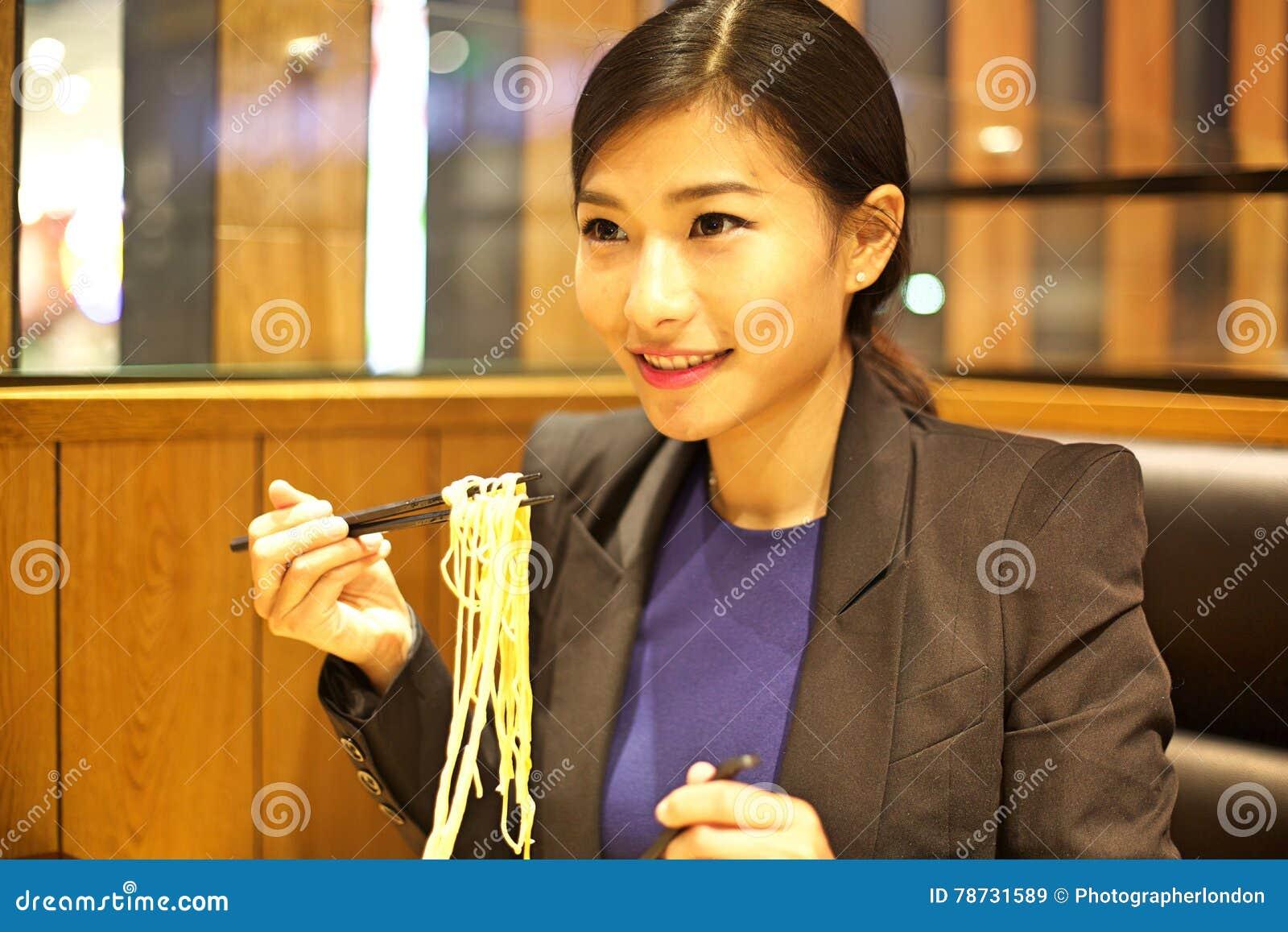 Kinesisk kvinna som äter nudlar i restaurang
