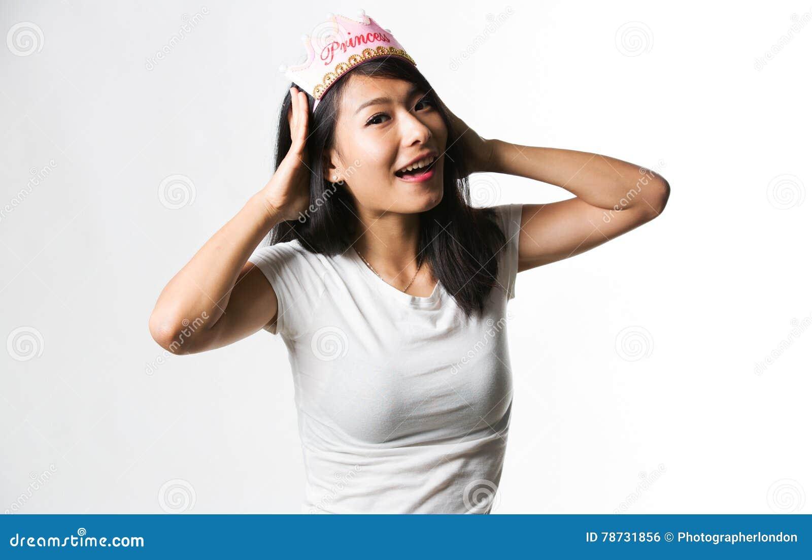 Kinesisk kvinna som har gyckel med en prinsessakrona