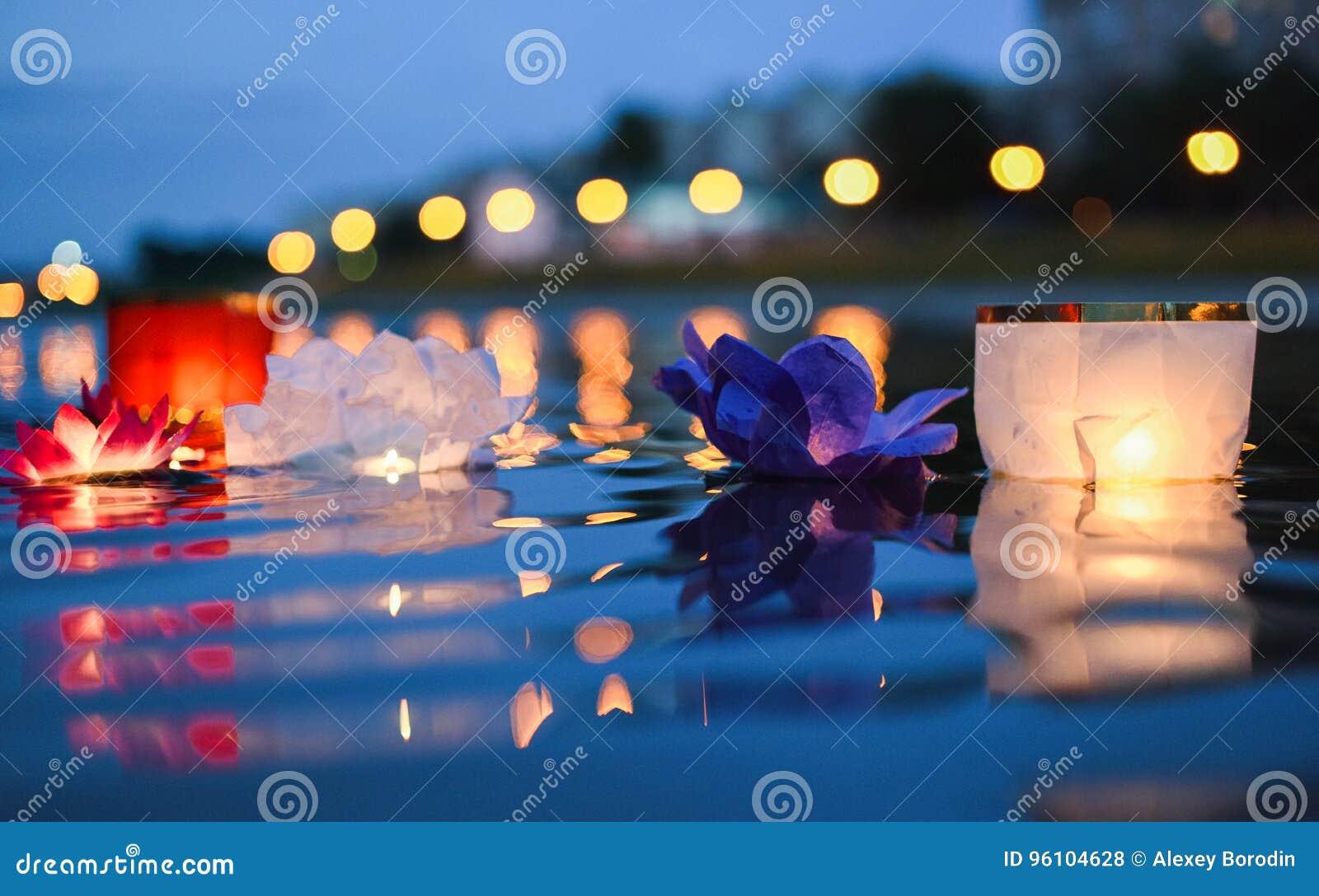 Kinesiska lyktor som svävar i floden på natten med staden, tänder