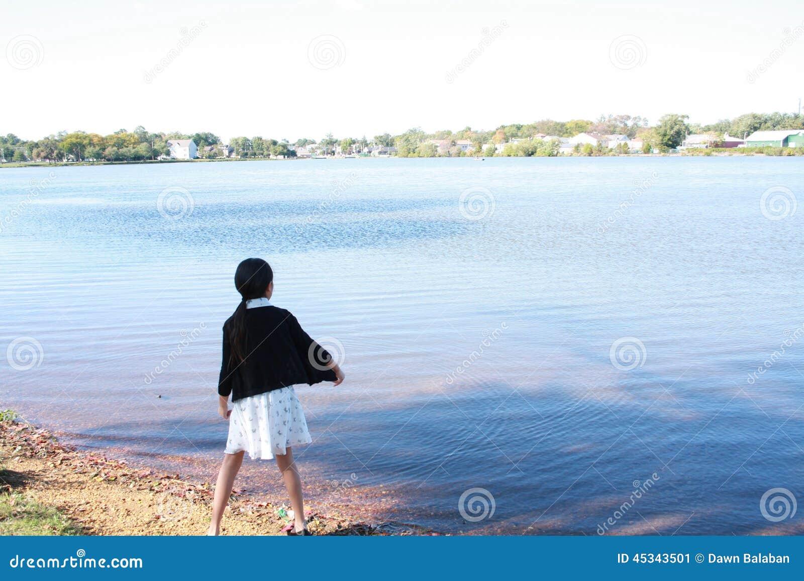 Kinesiskt flickabarn som kastar stenen i vattnet