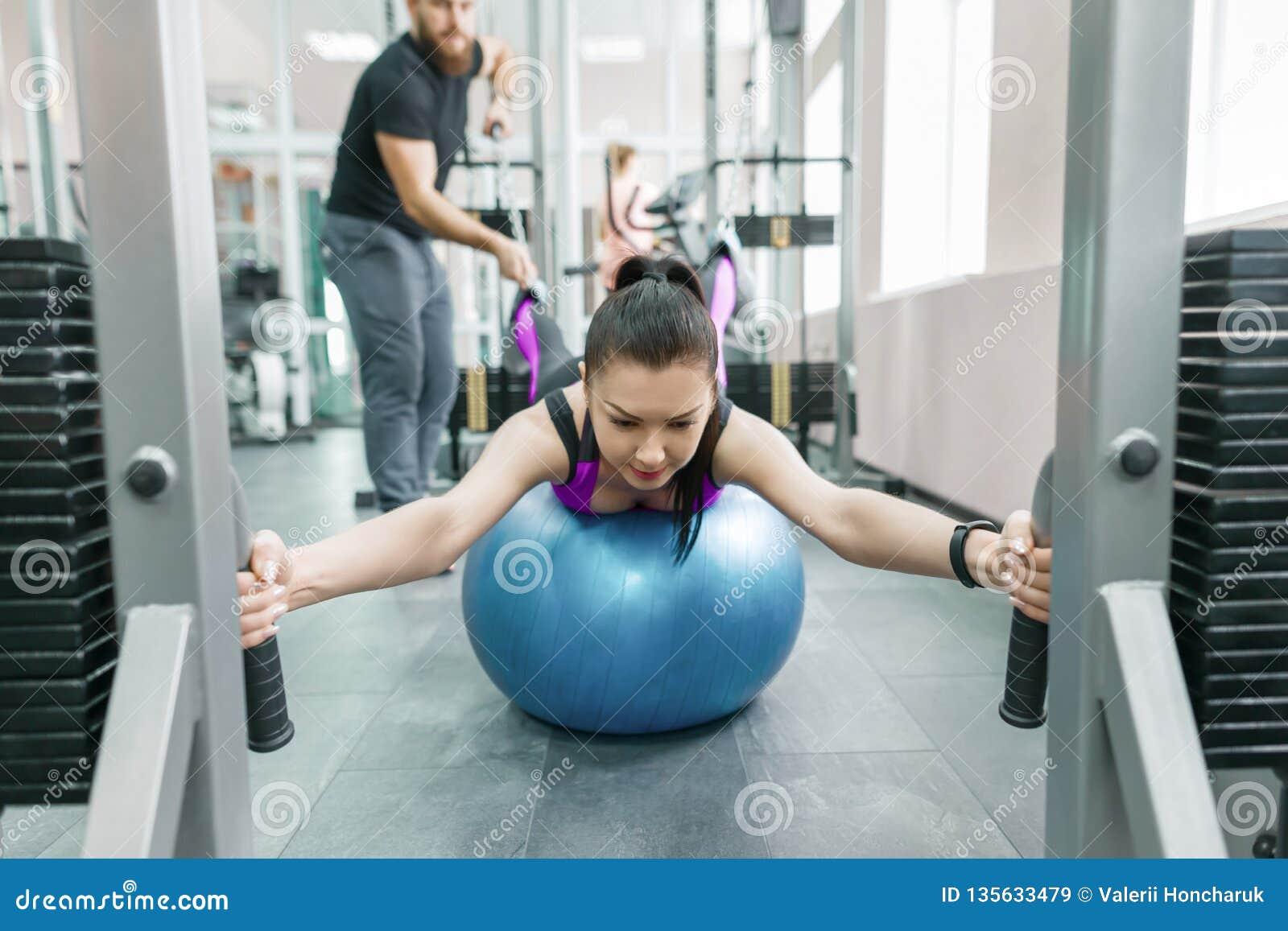 Kinesisteknologi, kinesitherapy, sund livsstil Ung kvinna som gör rehabiliteringövningar med personligt använda för instruktör