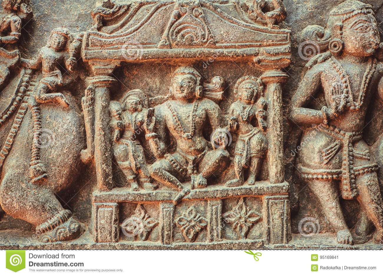 King or reach man sitting on sculpured stone relief
