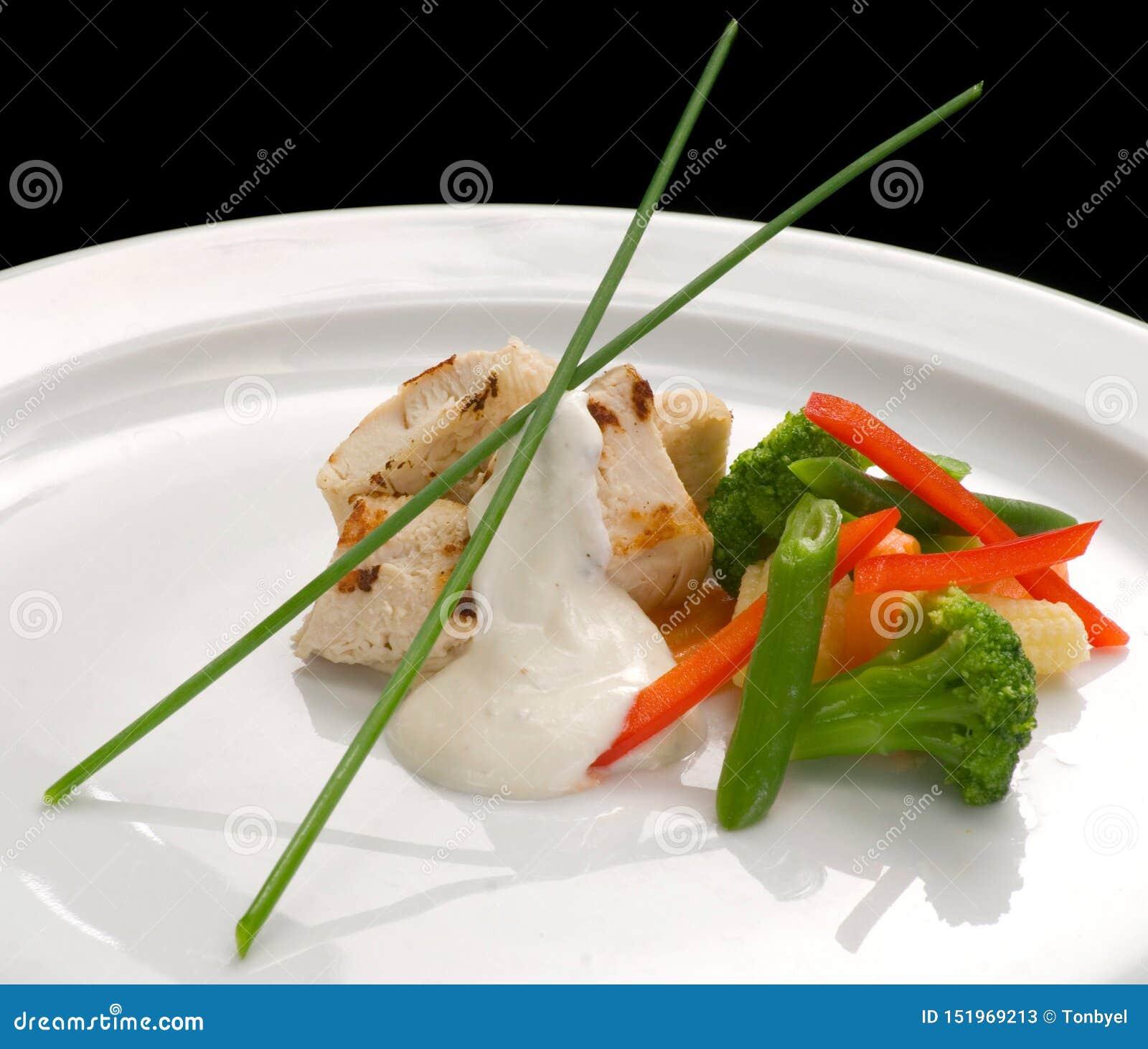 Kippenfilet, gestoomde groenten en yoghurtsaus op een plaat, close-up