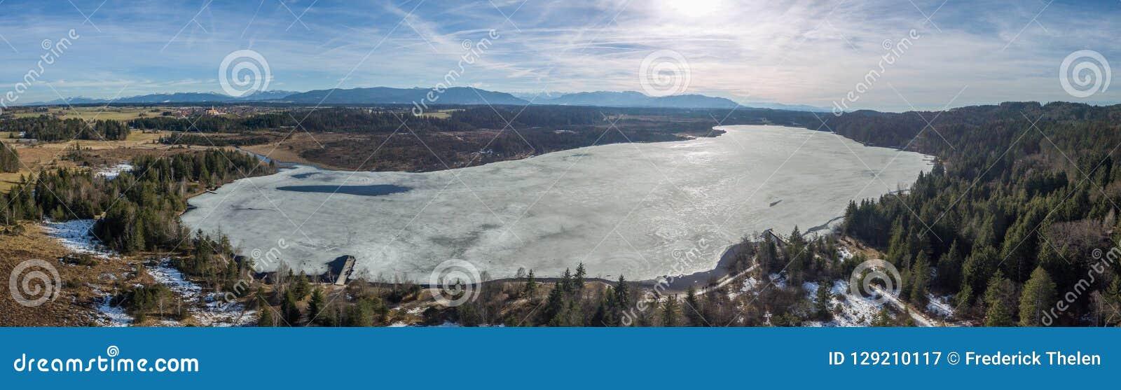 Kirchsee See, Bayern, mit Alpen im Hintergrund, im Frühjahr Winter