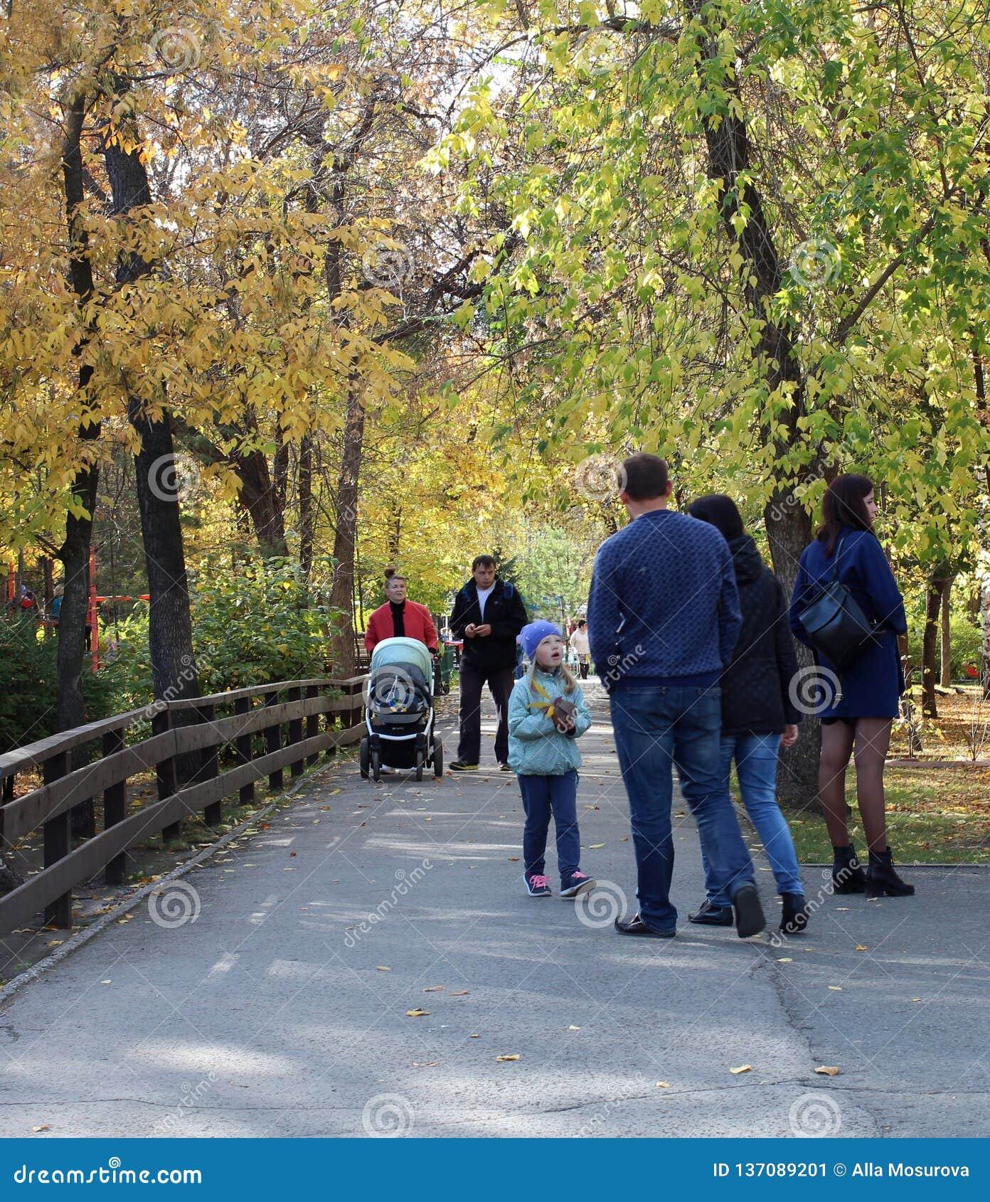Men women and children walk in a beautiful Park in autumn Kirov Park Novosibirsk summer 2018