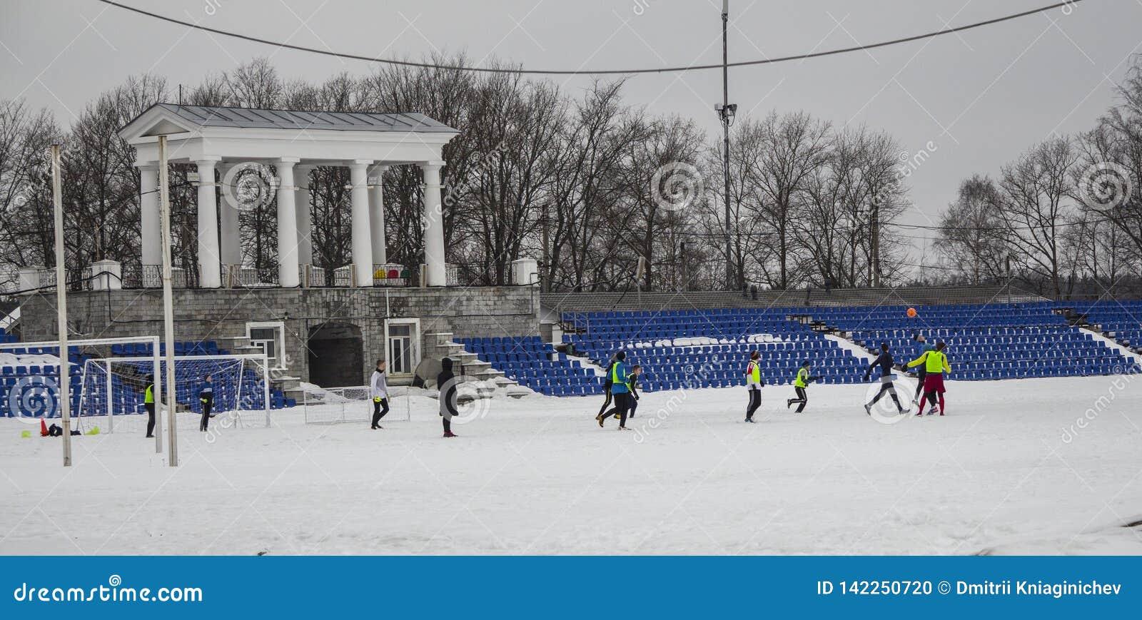 Kirovsk, Rusland, 17 Maart, 2019 De kinderen spelen voetbal in het stadion op de sneeuw