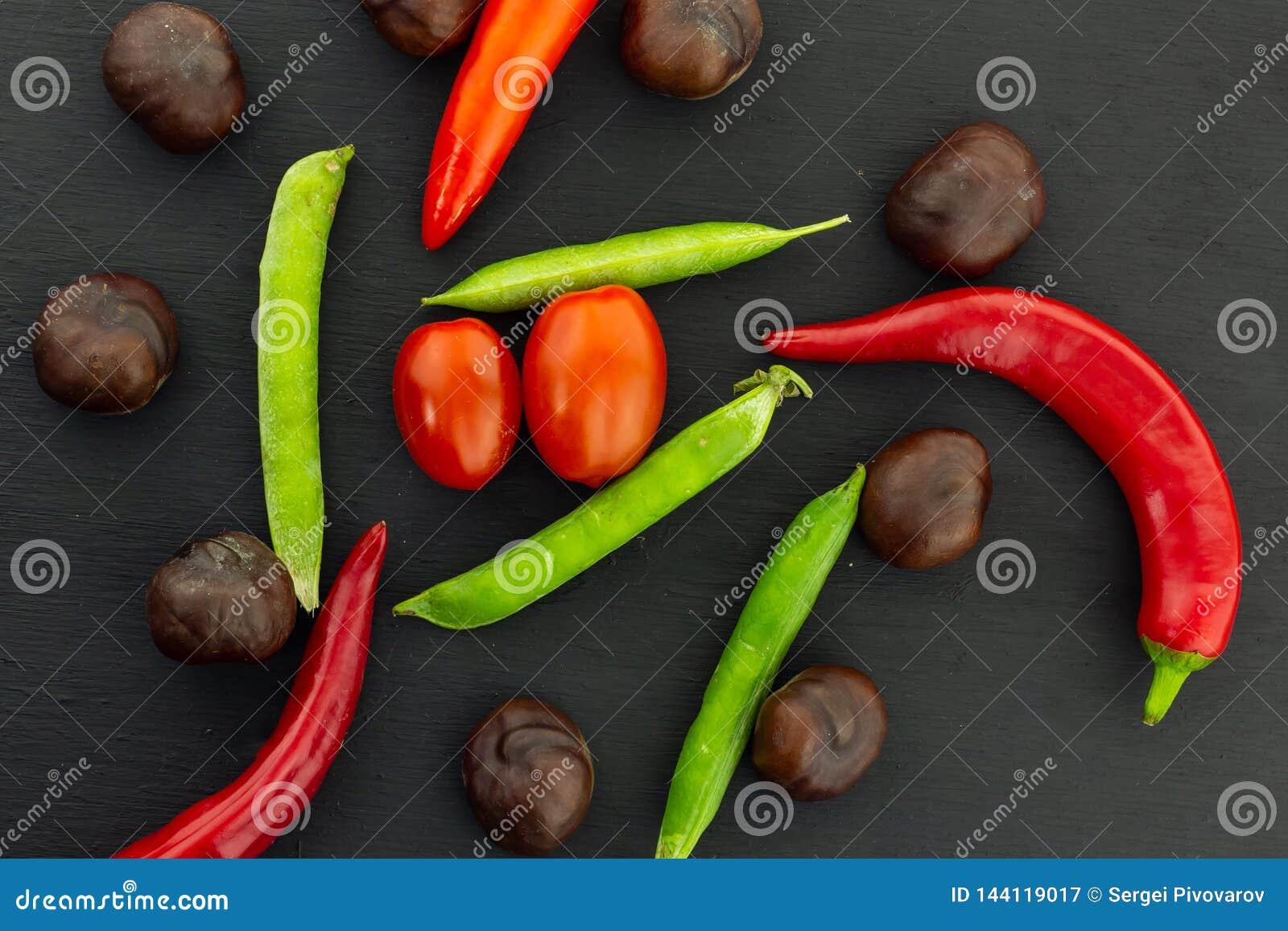 Kirschtomaten-Hülsenerbsen-Kastanienkastanie, die Gemüsesatz geschmackvoll auf schwarzem Hintergrundkontrast-Menüentwurf viel ist