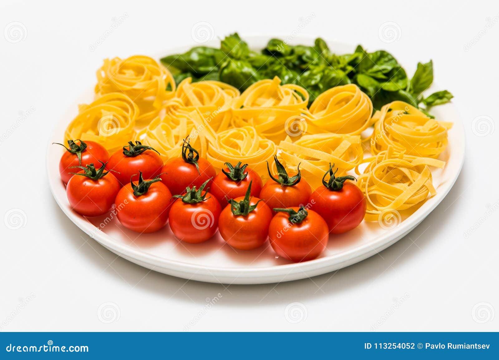 Kirschtomaten, Spaghettis und frischer Basilikum auf einer Servierplatte auf einem weißen Hintergrund