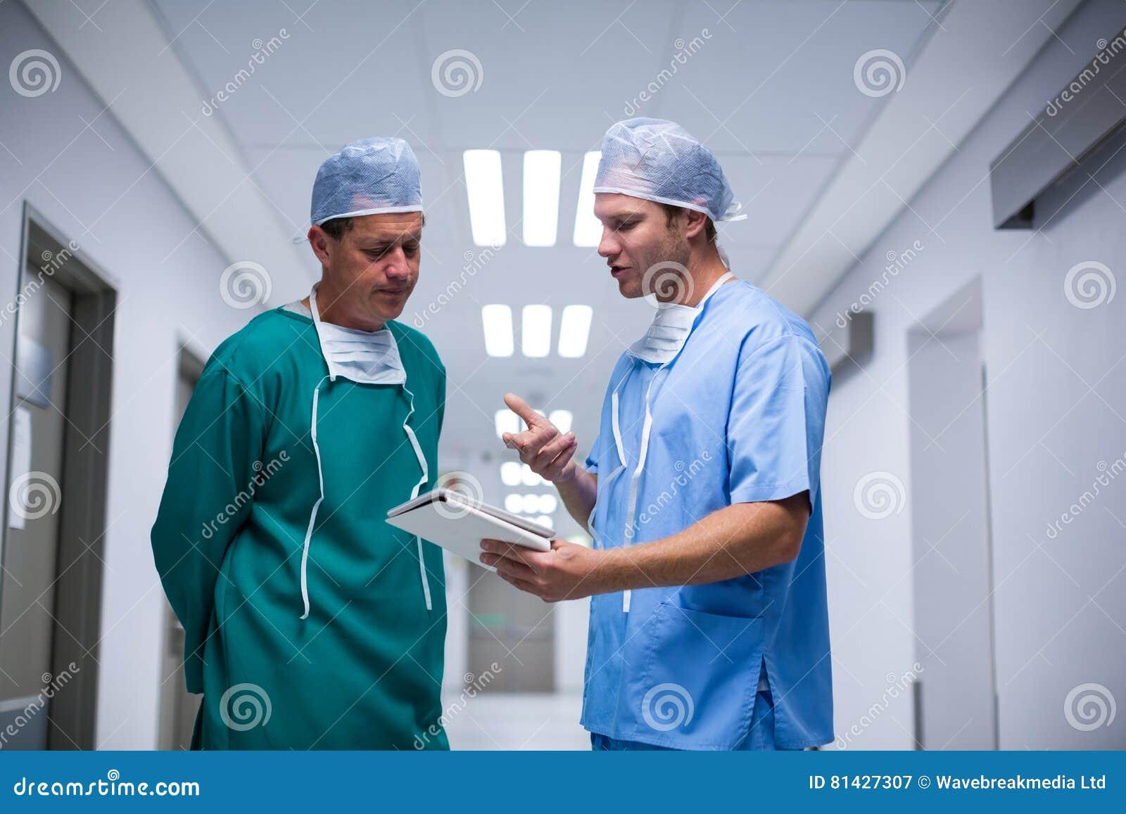 Kirurg och sjuksköterska som har diskussion över den digitala minnestavlan i korridor