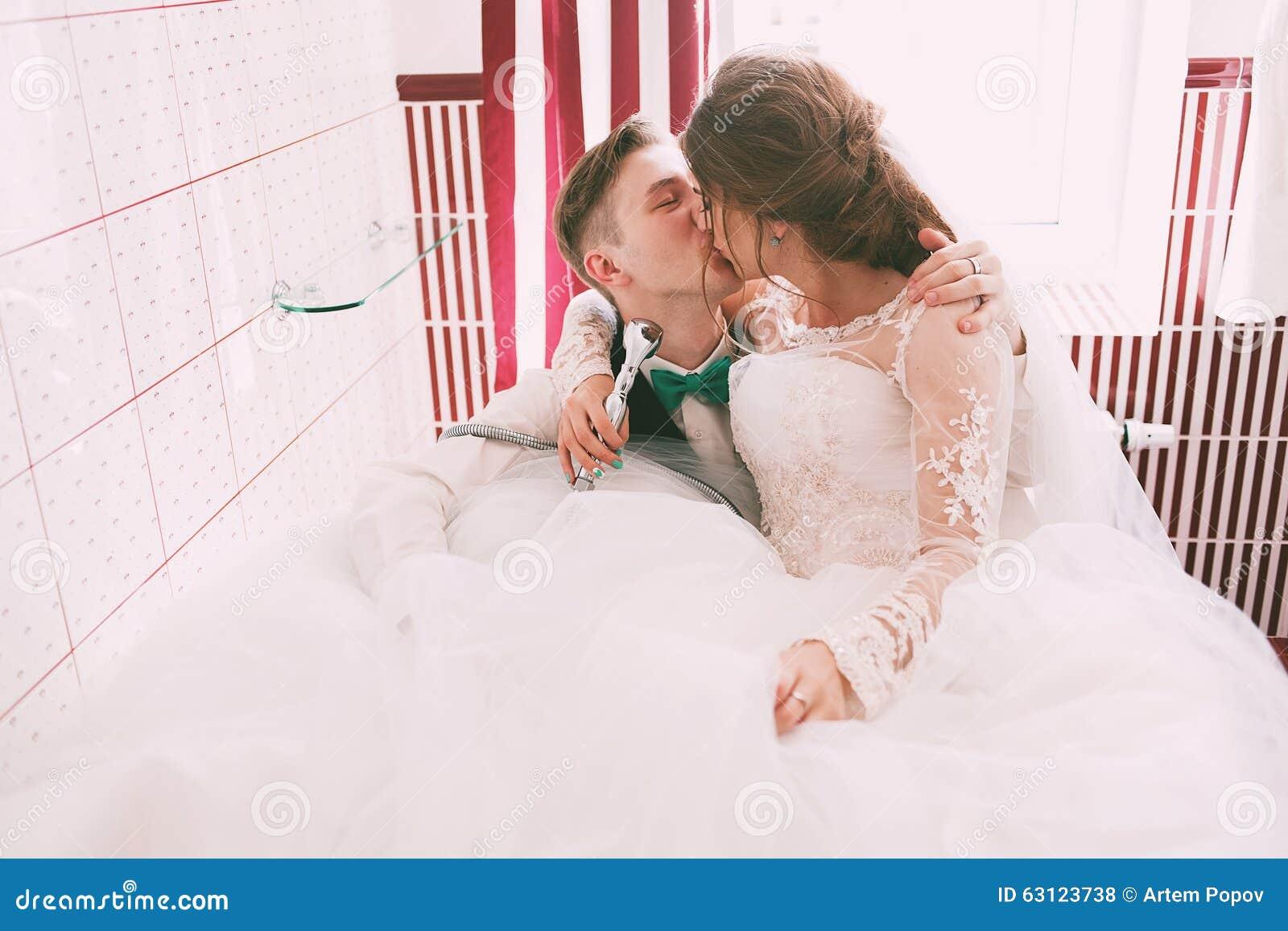 Kissing Bride And Groom Having Fun In Bathroom Stock Photo