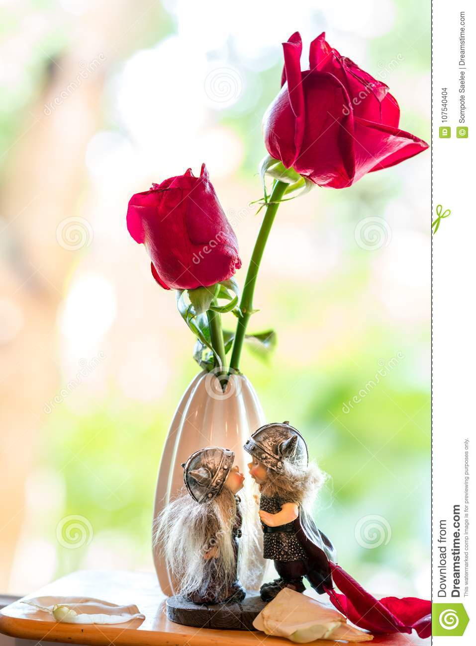 kissing dolls under two red roses with soft focus background