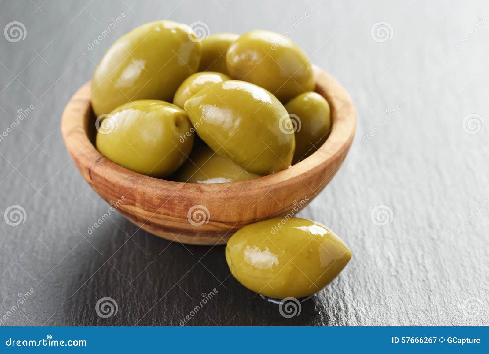 Kiszone gigantyczne zielone oliwki w oliwnym pucharze na łupku