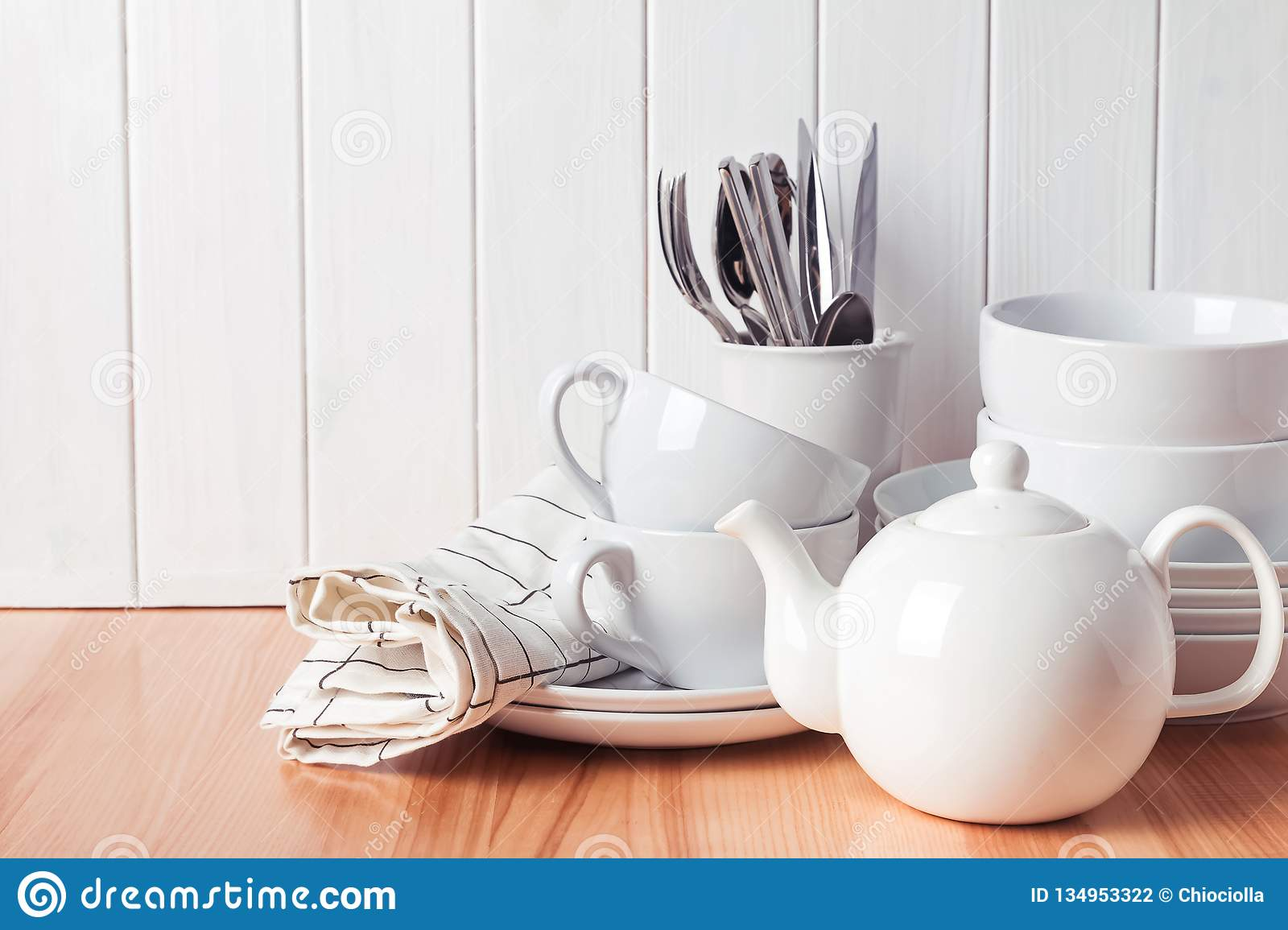 Different tableware, plates, cups standing near the white wooden wall