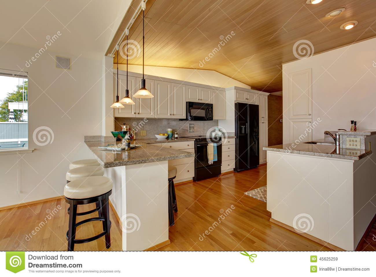 Cabinets with black appliances granite counter top with bar stools
