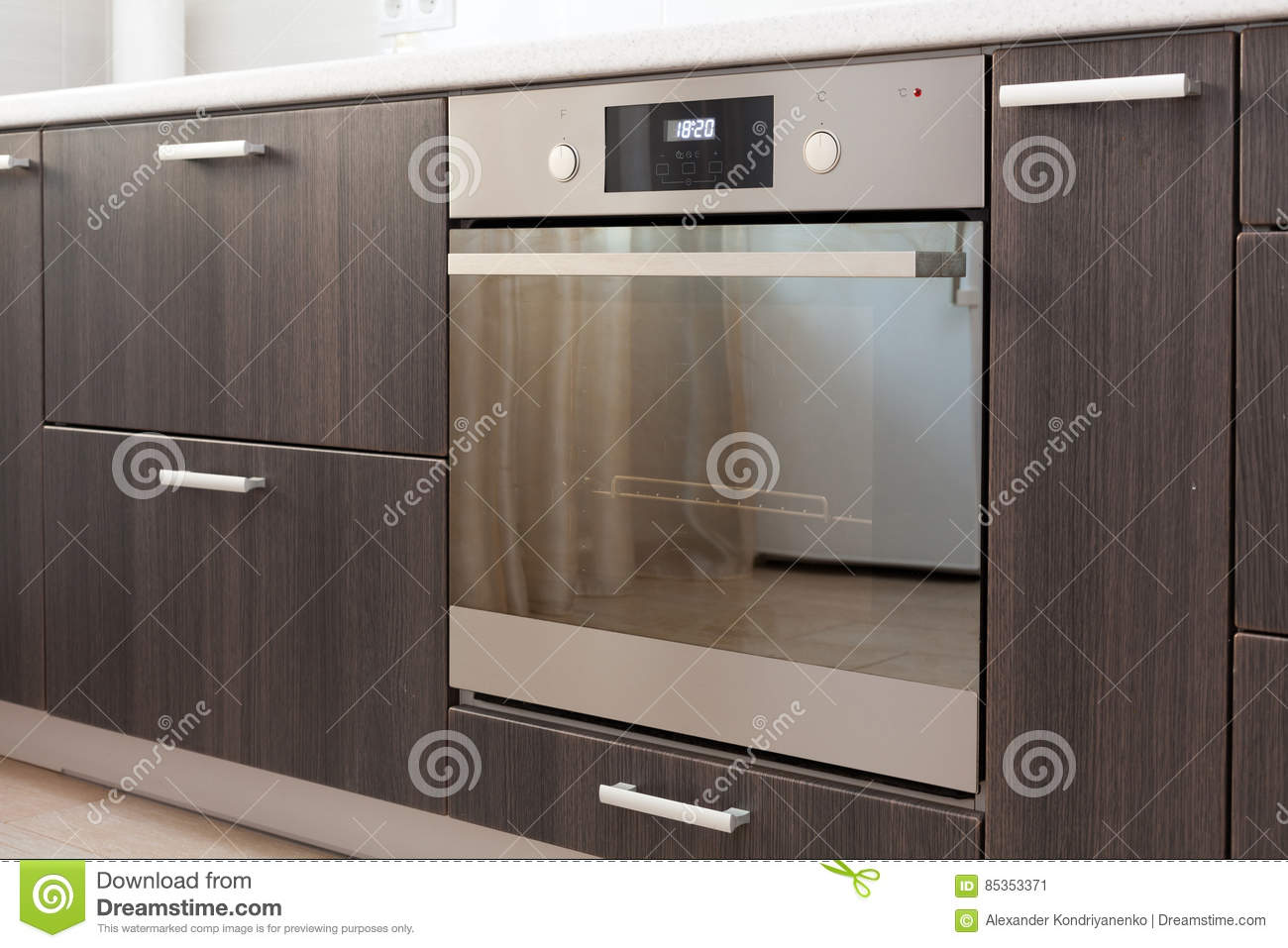 Kitchen cabinets with metal handles and built-in electric oven.