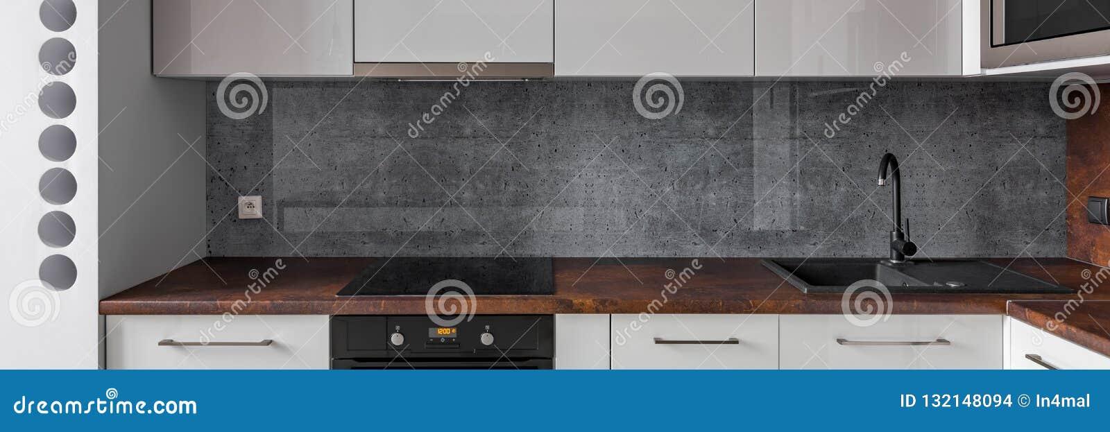 - Kitchen With Granite Worktop And Concrete Backsplash Stock Photo