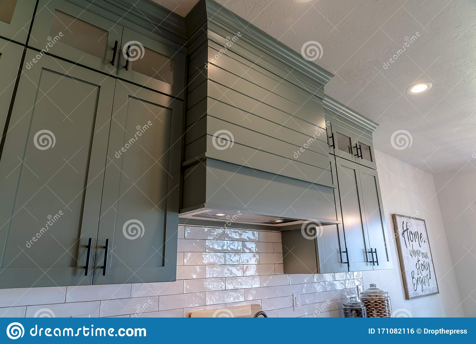 - Kitchen Interior With Hanging Cabinets Against Tile Backsplash And