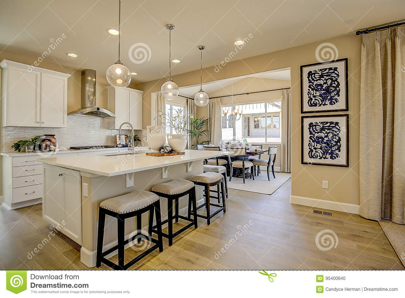 Modern Kitchen With White Cabinets Wood Floors Beige Walls And Dining Room Off To Side