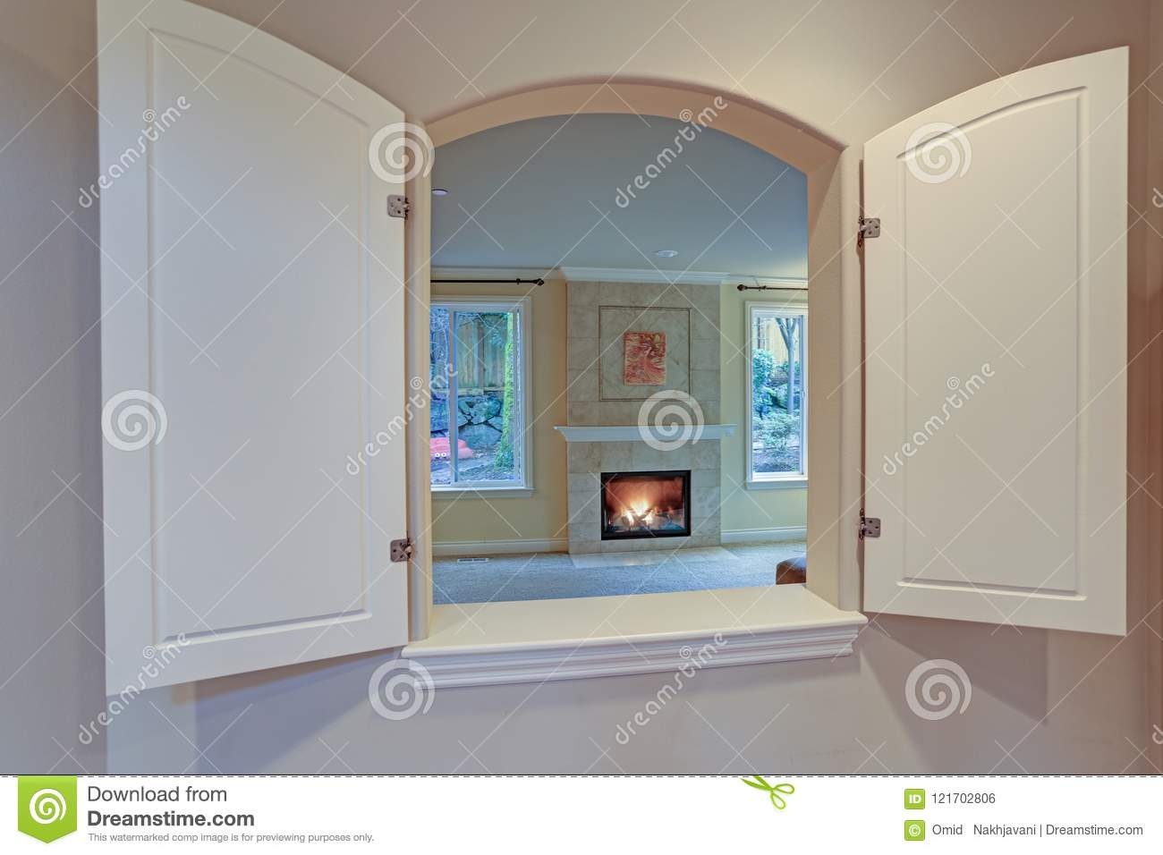 Kitchen pass through window opens to a living room