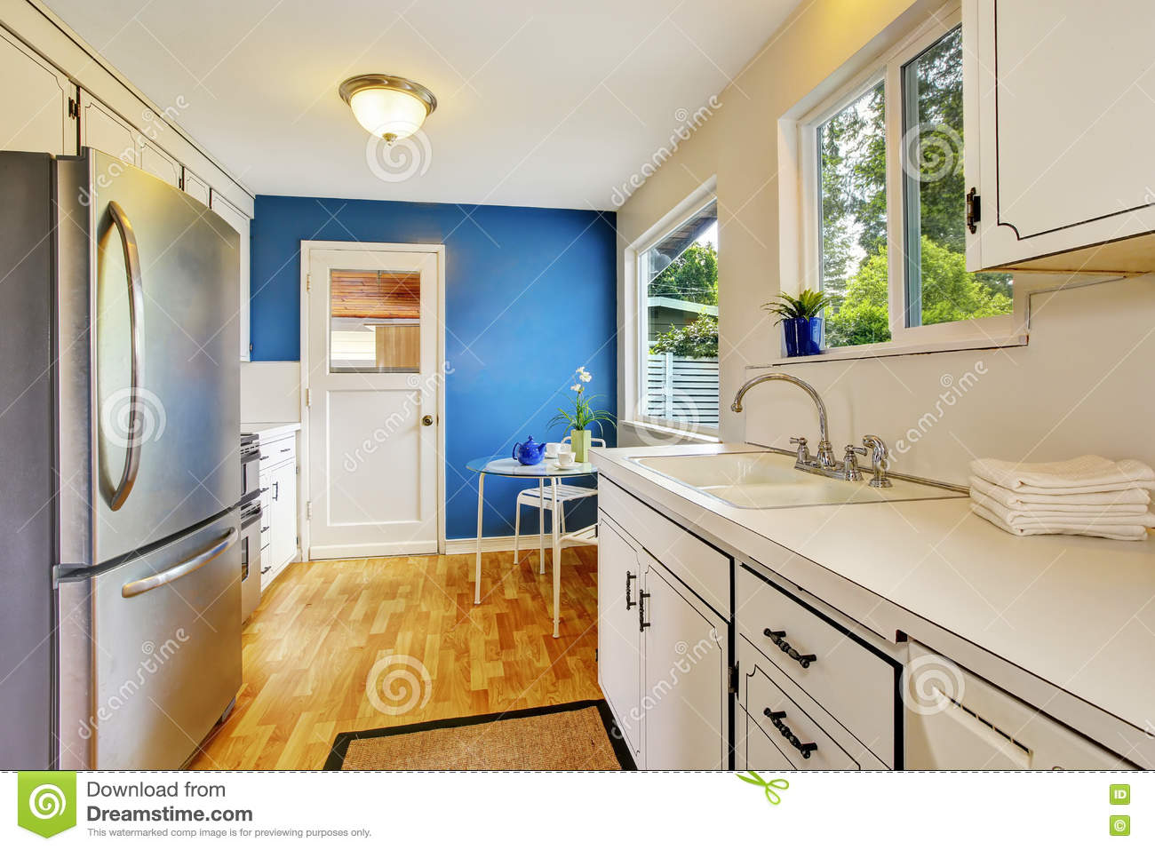 Kitchen Room With White Cabinets Blue Walls And Glass Able