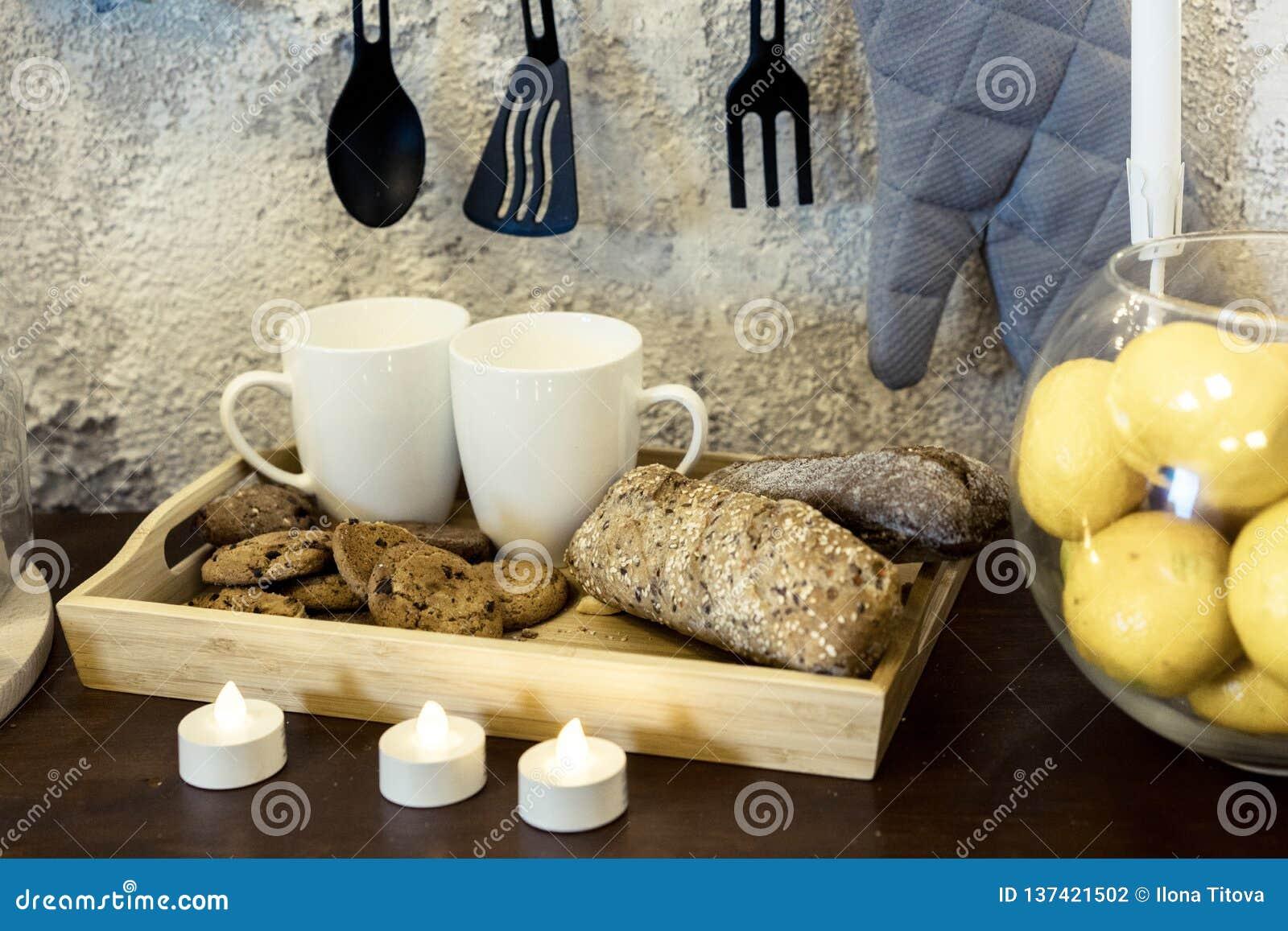 Kitchenware Due tazze di caffè macchiato su una tavola davanti ad un muro di cemento Le tazze sono in un vassoio con pane Candele