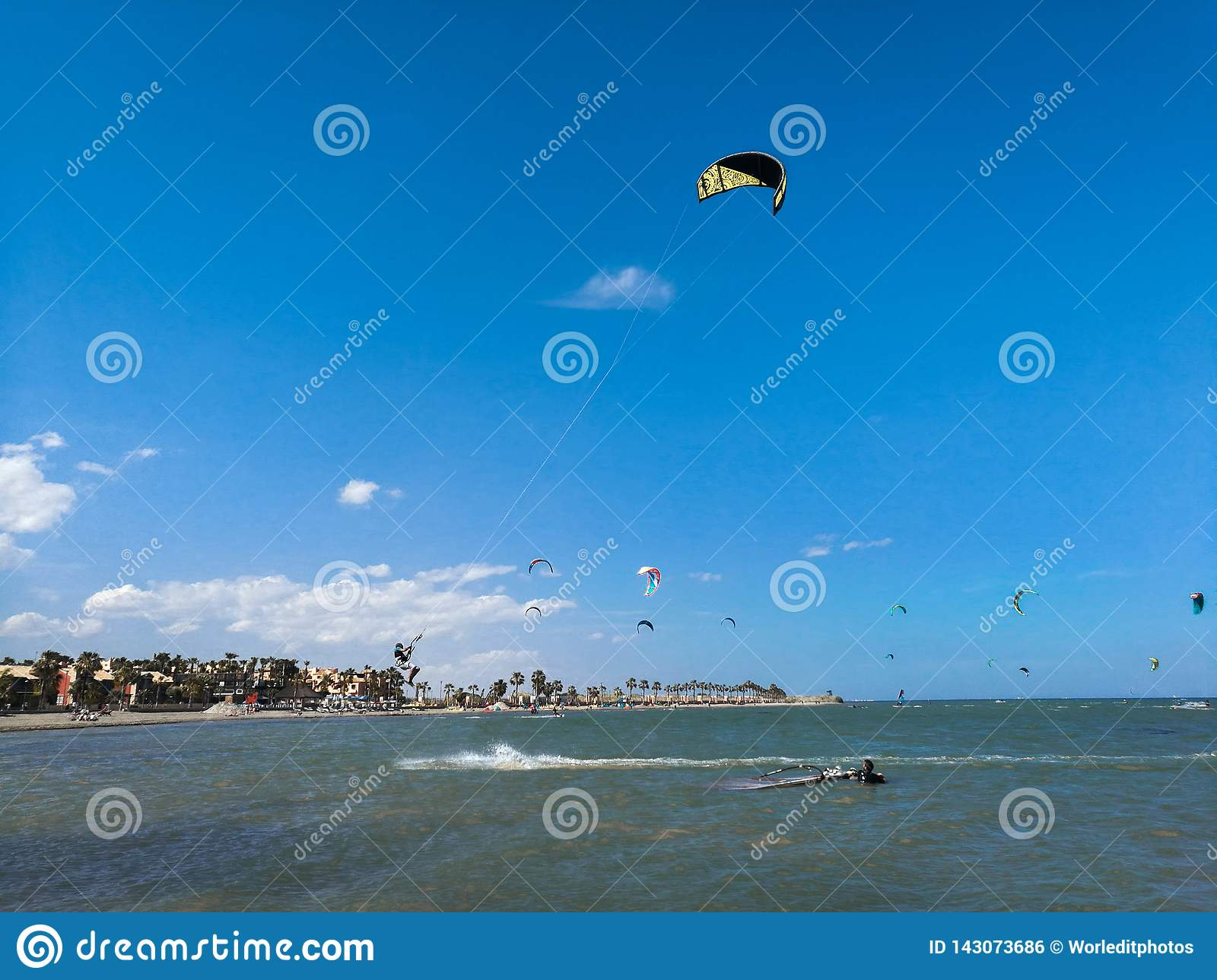 Kite boarding sportsman flying high with kite and kiteboard in boots in the blue sky, active sports and life style in spanish