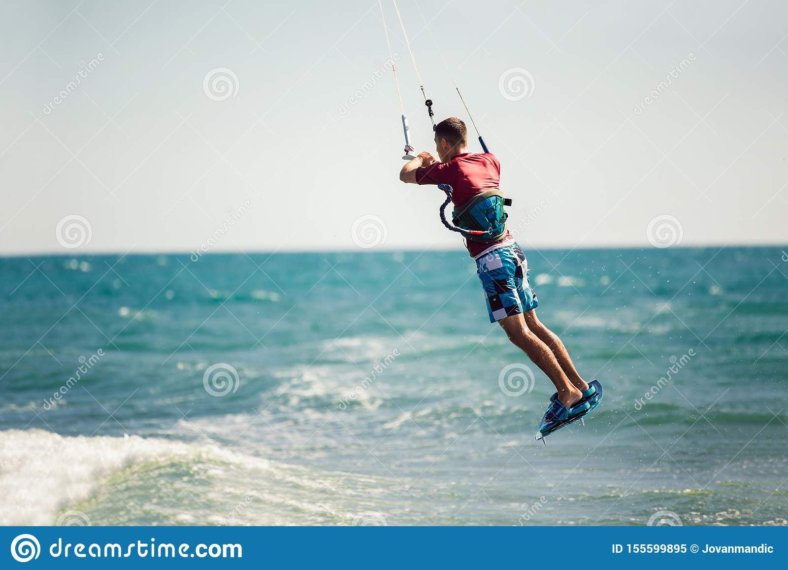 Kiter makes the difficult trick on a beautiful background. Kitesurfing Kiteboarding action photos man among waves