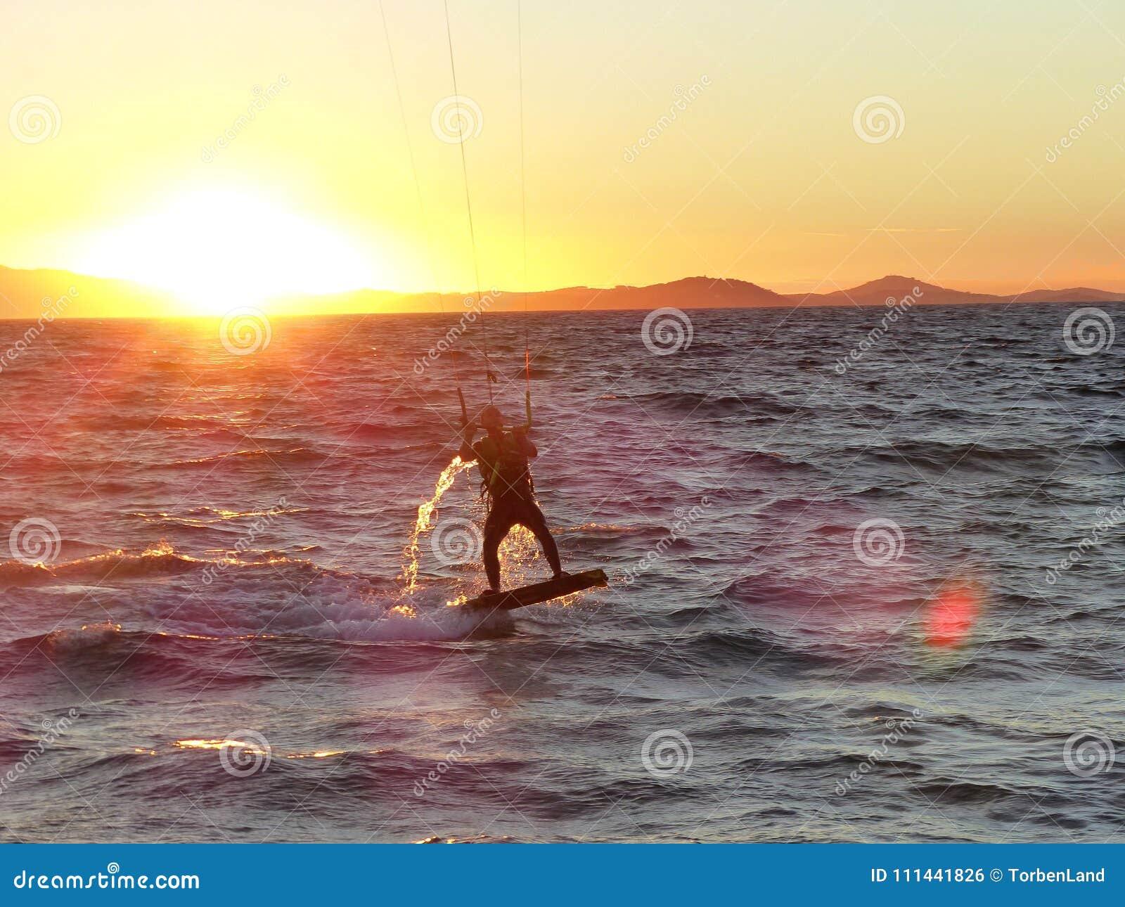 Kitesurfer冲浪并且跳进日落在Hyeres,法国
