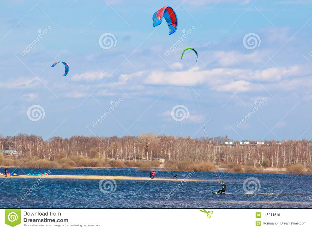 Kitesurfing in the flooded meadows during the high water on a bright sunny day.