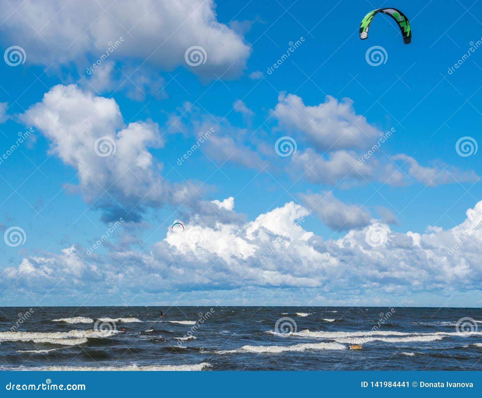 Kitesurfing Fotos de la acción de Kiteboarding El hombre entre ondas va rápidamente