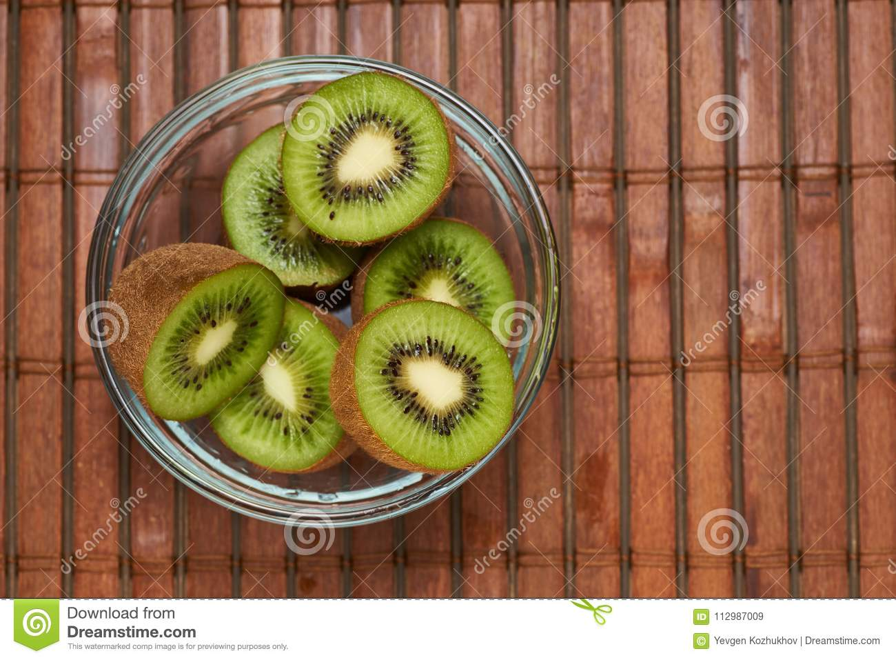 Kiwi in a glass plate on a bamboo background