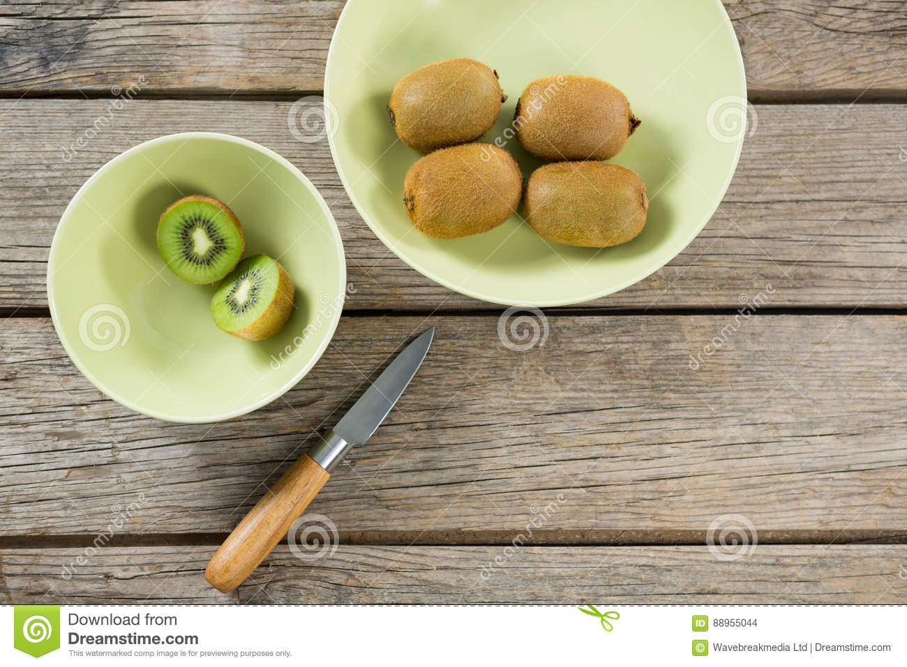 Kiwis in bowl with knife on wooden table