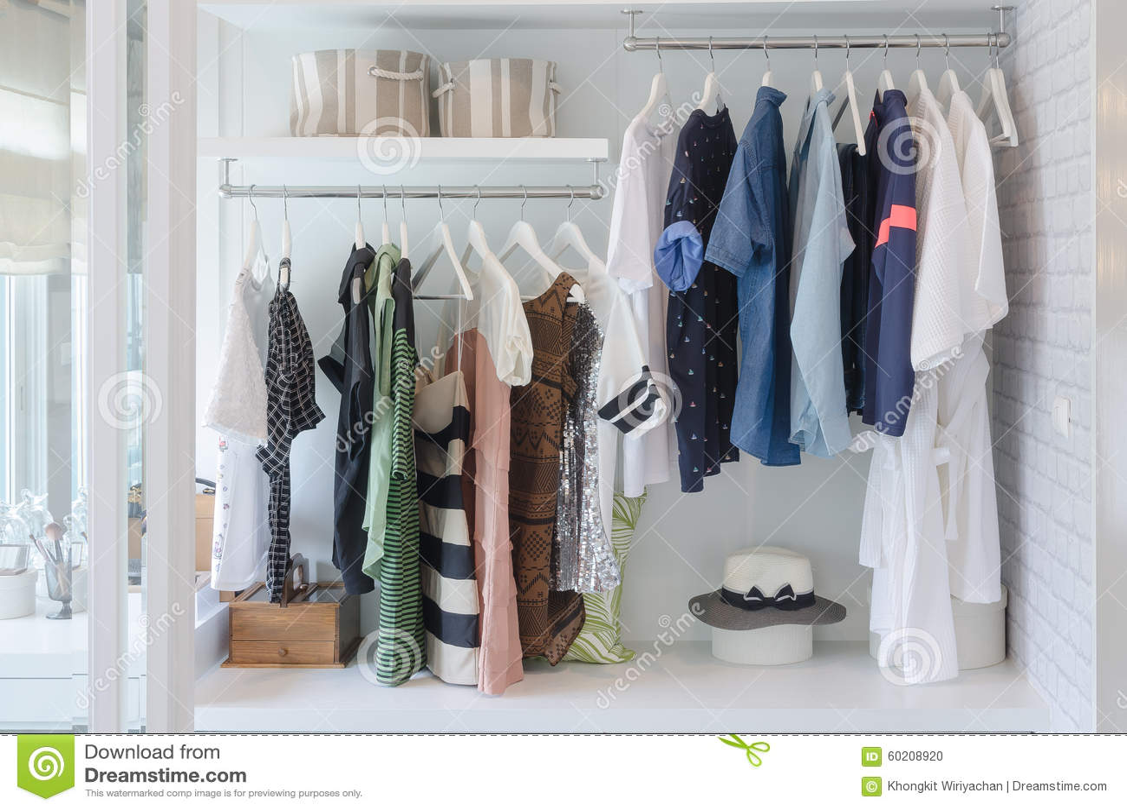 Kläder som hänger i garderob med hatten