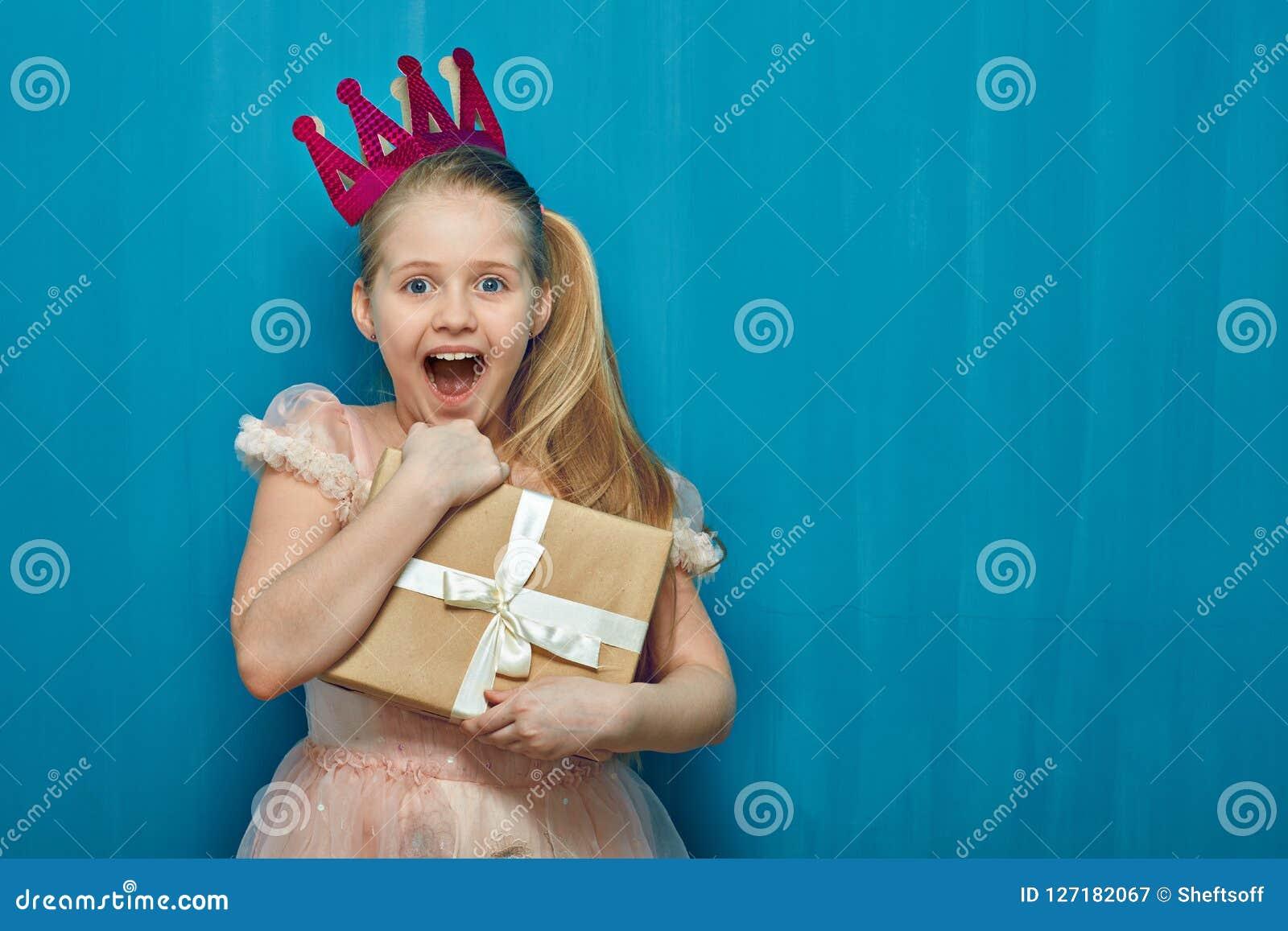 Klär krönar bärande rosa färger för lycklig överraskande flicka och den hållande gåvan