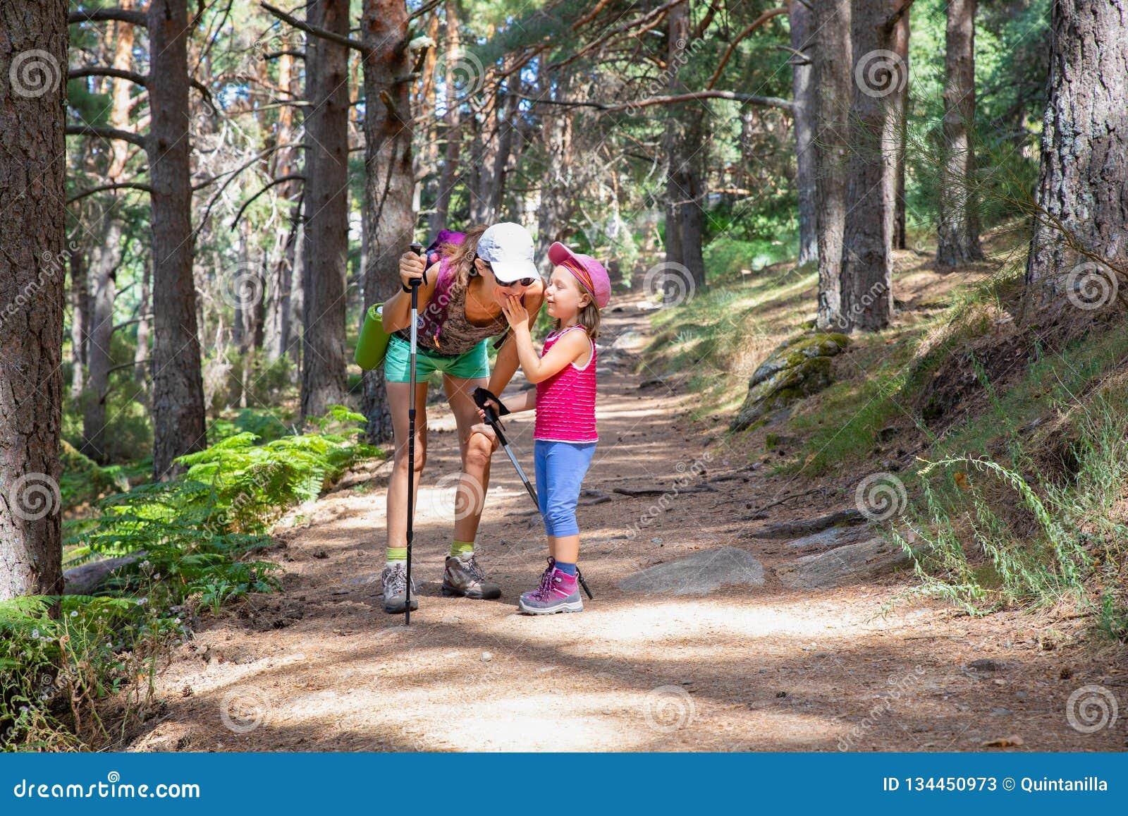 Klättra i berg det lilla barnet som skrattar och talar till kvinnan på en vandringsled i skog