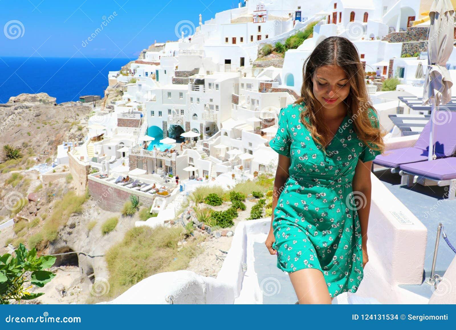 Klättrar den turist- lyckliga kvinnan för loppet trappan i Santorini, Cyclades öar, Grekland, Europa Flicka på sommarsemester