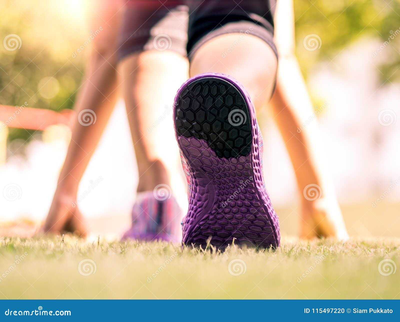 Klaar Regelmatig gaat Close-up van loopschoenen op gras, jonge dame op beginpositie en het gaan in park lopen