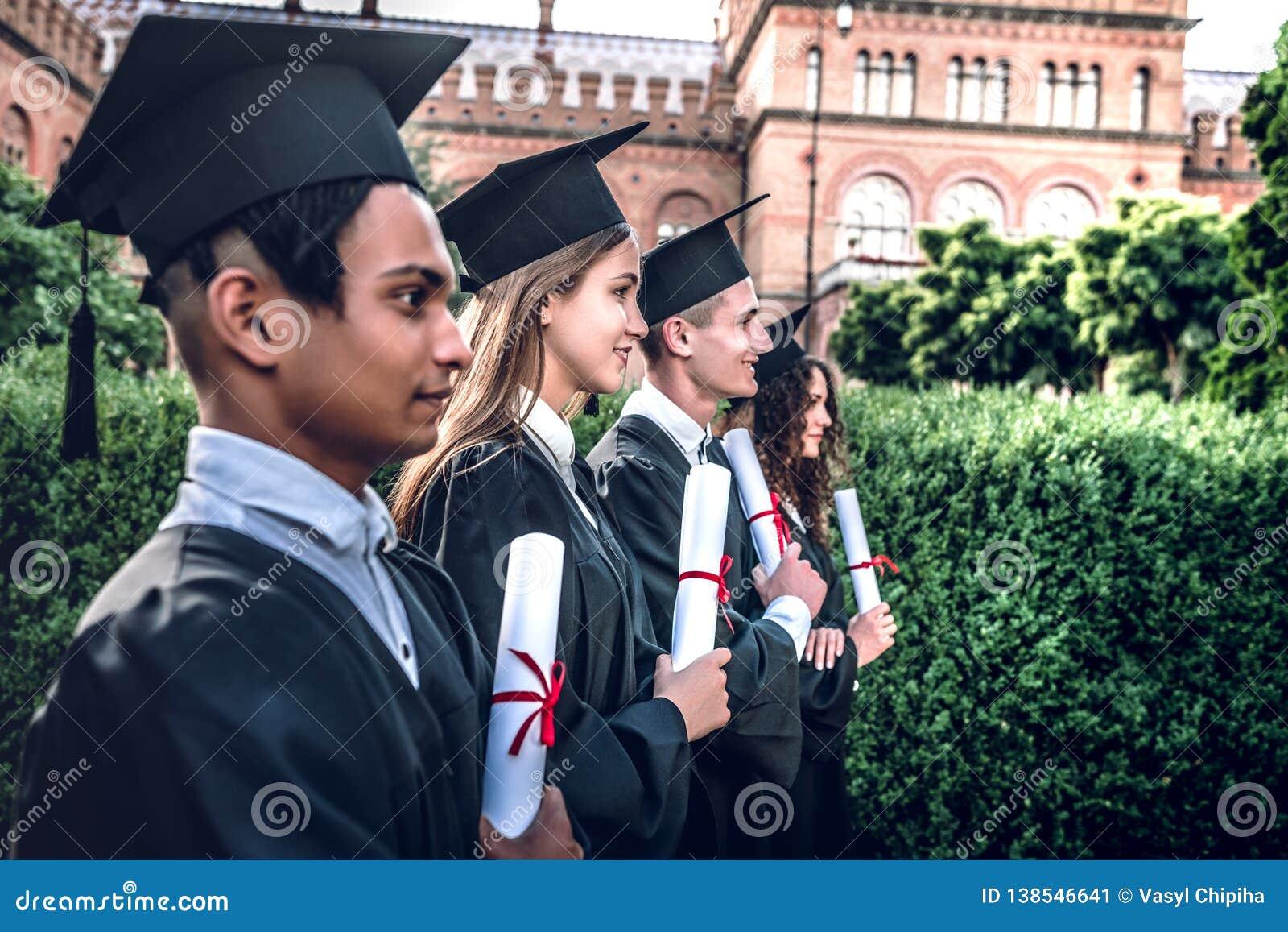 Klaar voor nieuw begin! De gelukkige gediplomeerden bevinden zich op een rij op universiteit in openlucht in mantels met in hand