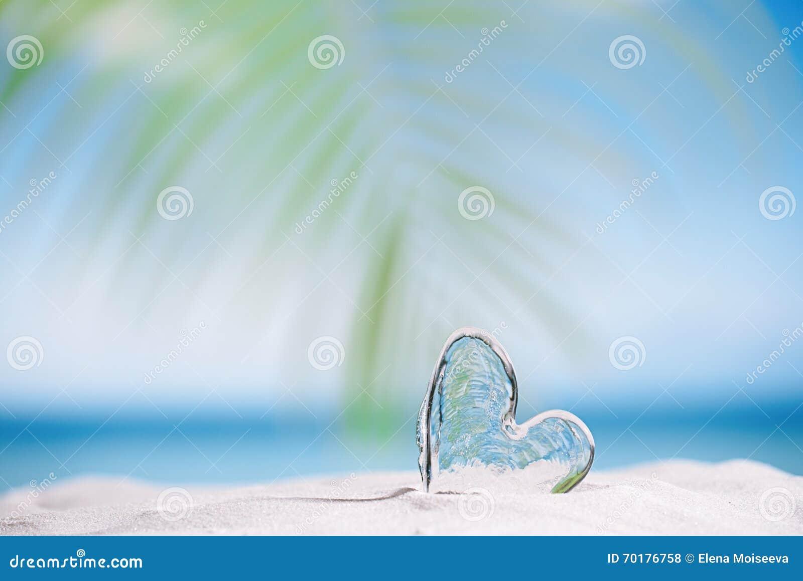 Klar glass hjärta på den vita sandstranden