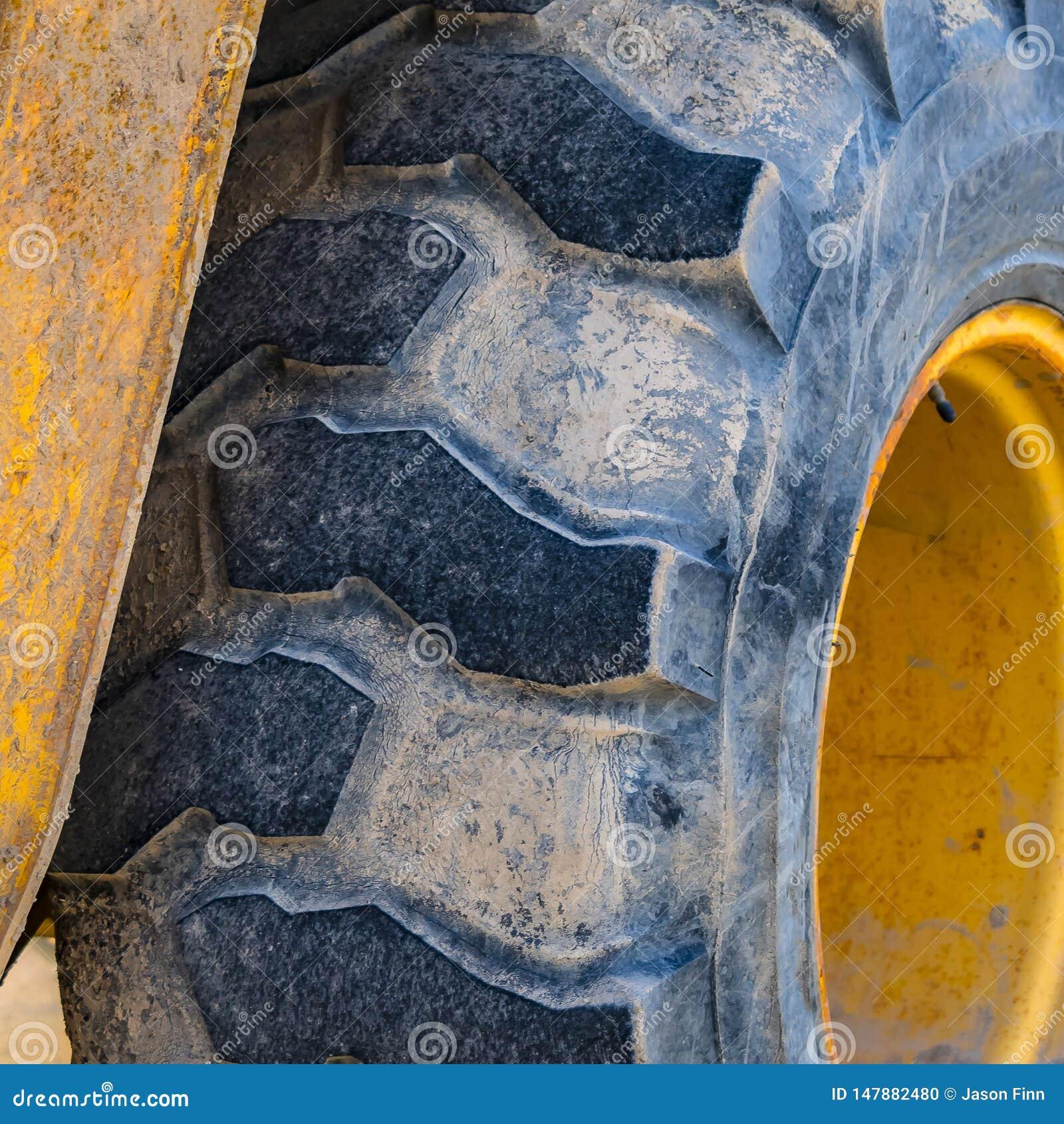 Klart fyrkantigt slut upp av de smutsiga hjulen av en riden ut laddare som parkeras på en solbelyst väg