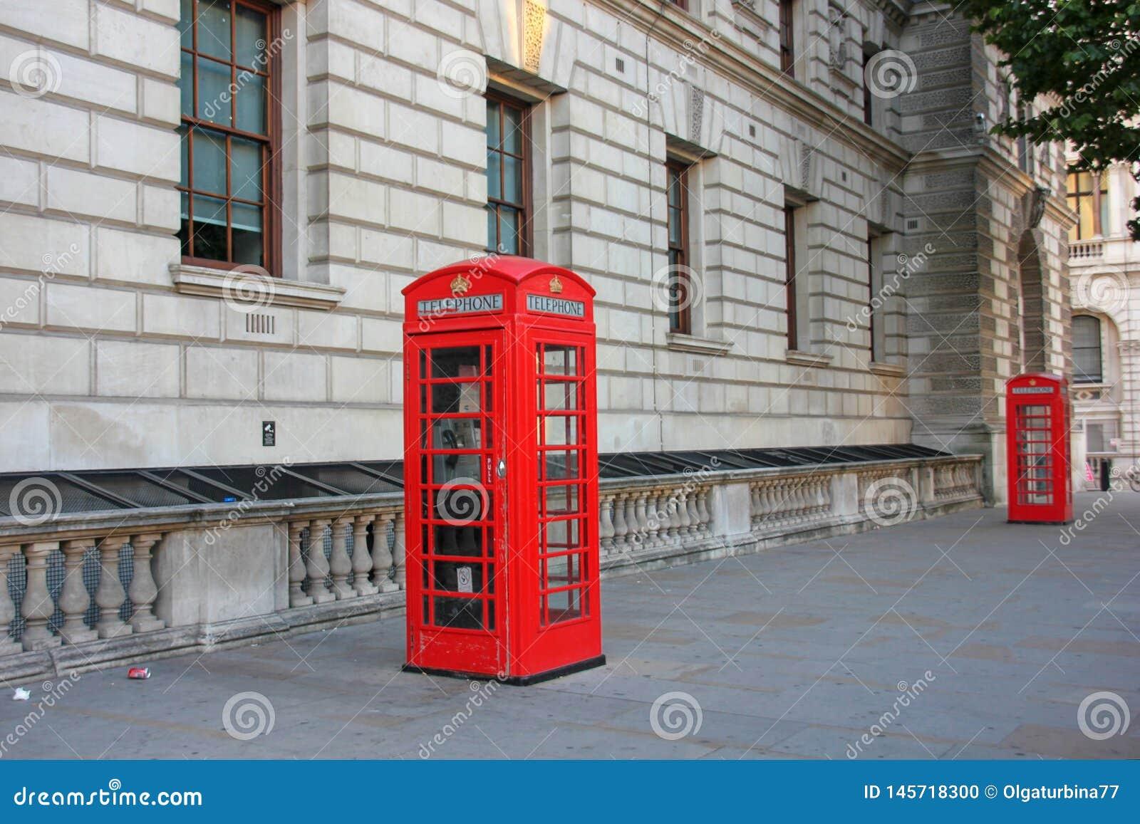 Klassieke Britse rode telefooncel op oude straat van Londen, het UK