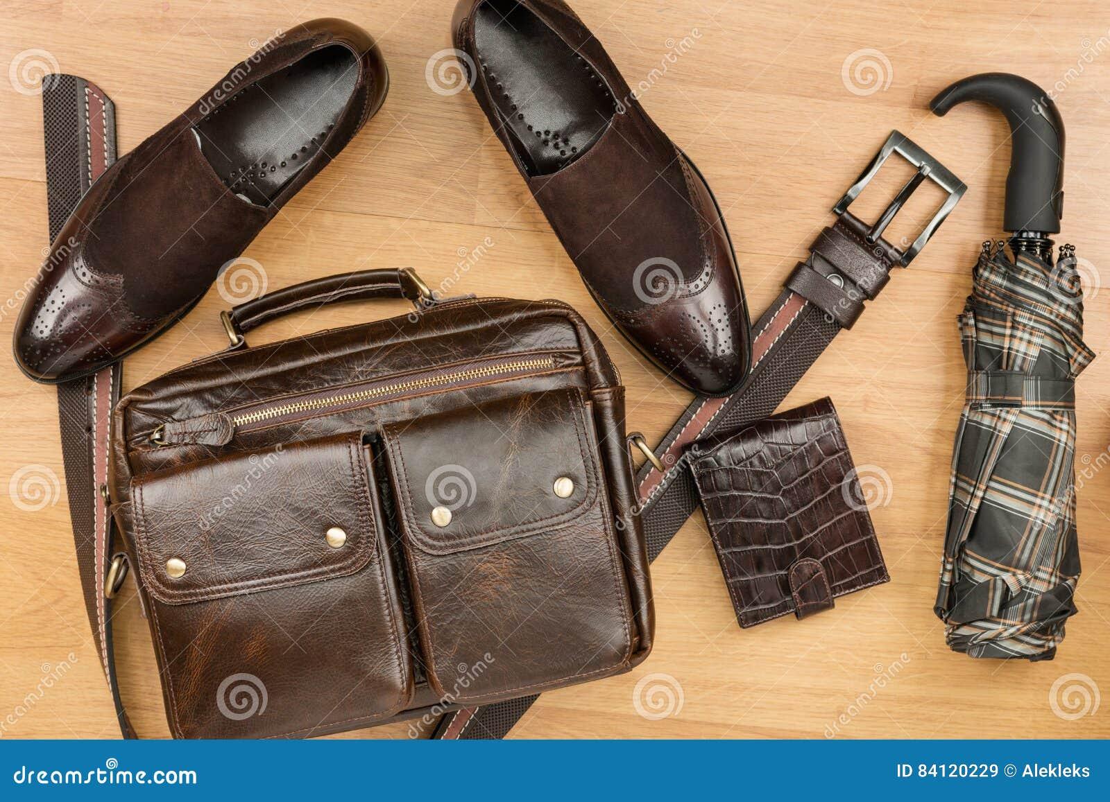 Klassieke bruine suèdeschoenen, aktentas, riem en paraplu op de houten vloer
