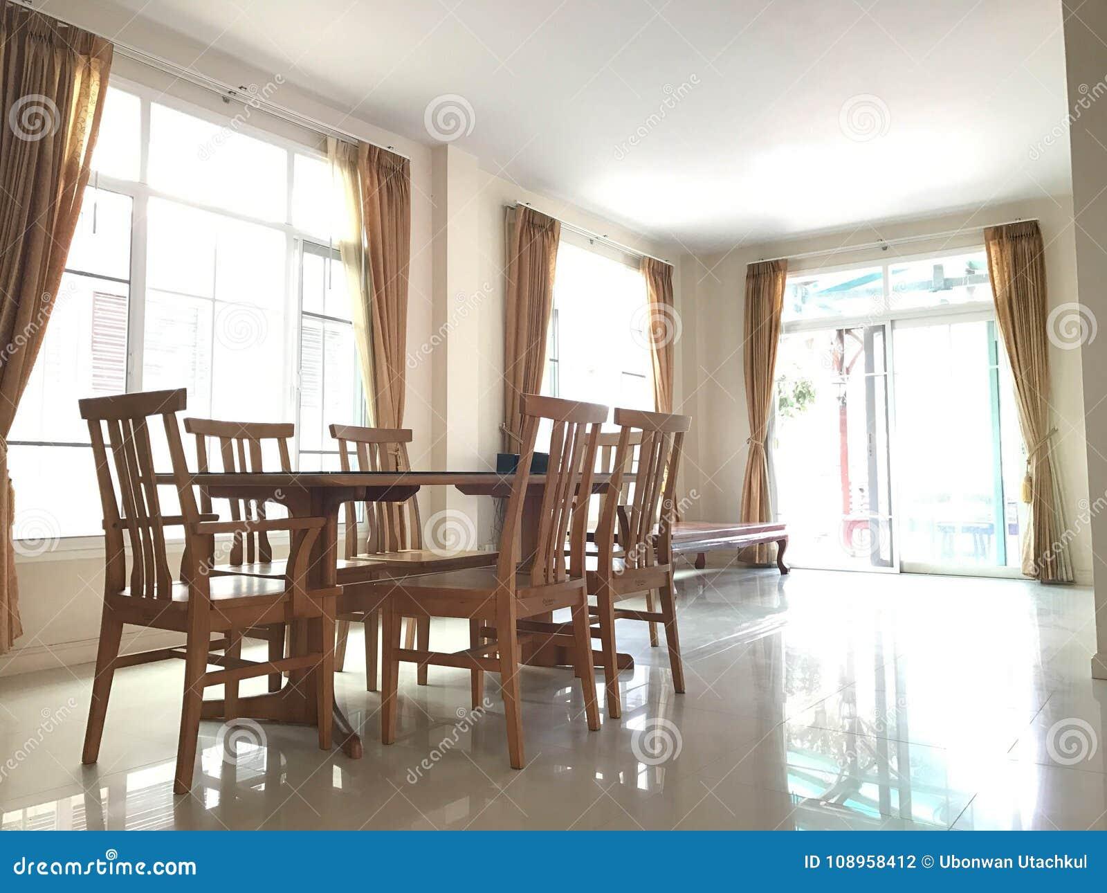 Klassieke lege houten eettafel in bruine gordijnwoonkamer stock foto